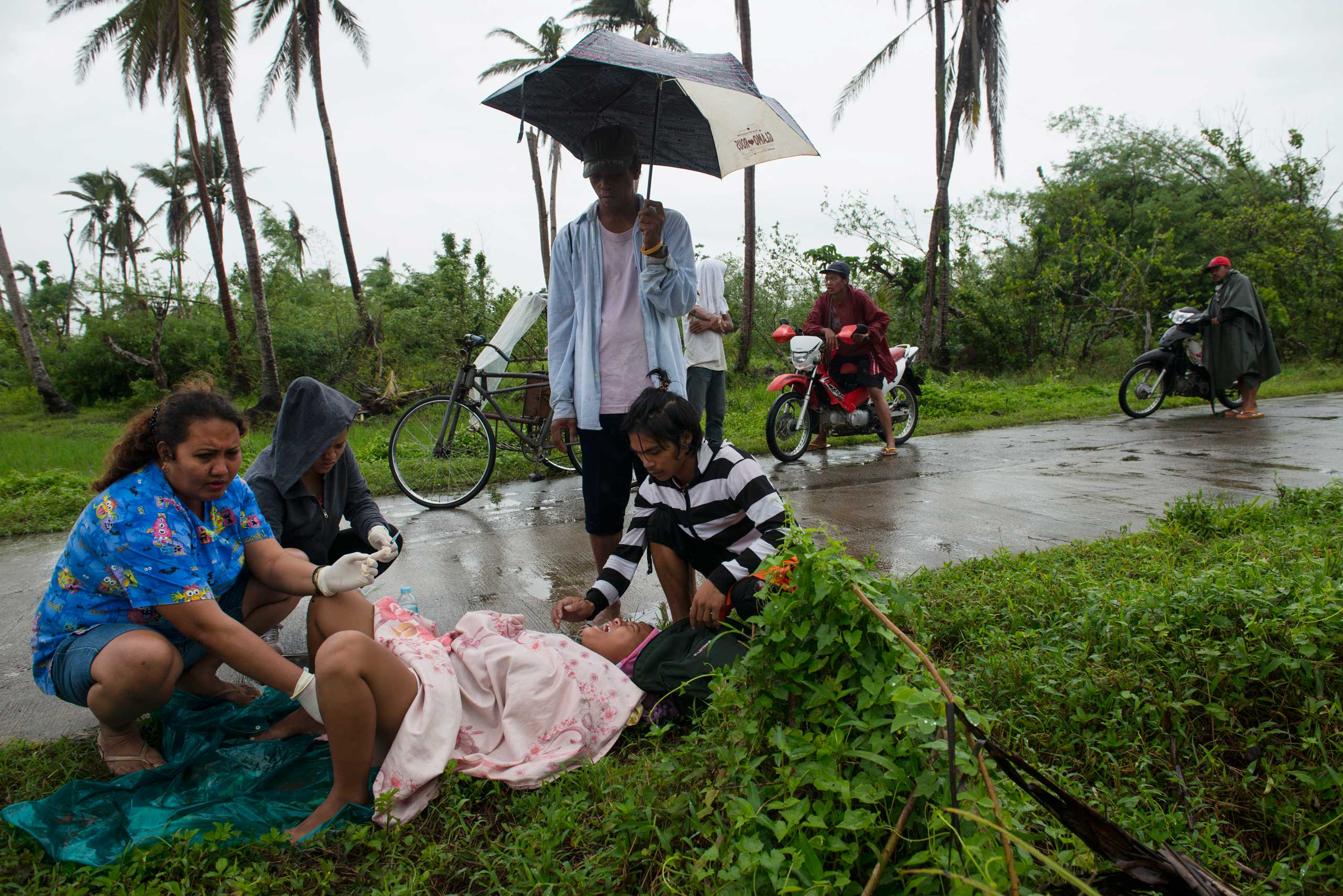 Midwife Norena Malate delivers the baby of Analyn Pesado, 18, as Analyn's husband, Ryan Bacate, 21, looks on on the side of the road in Tolosa, outside of Tacloban, in the Philippines, Jan. 11, 2014.