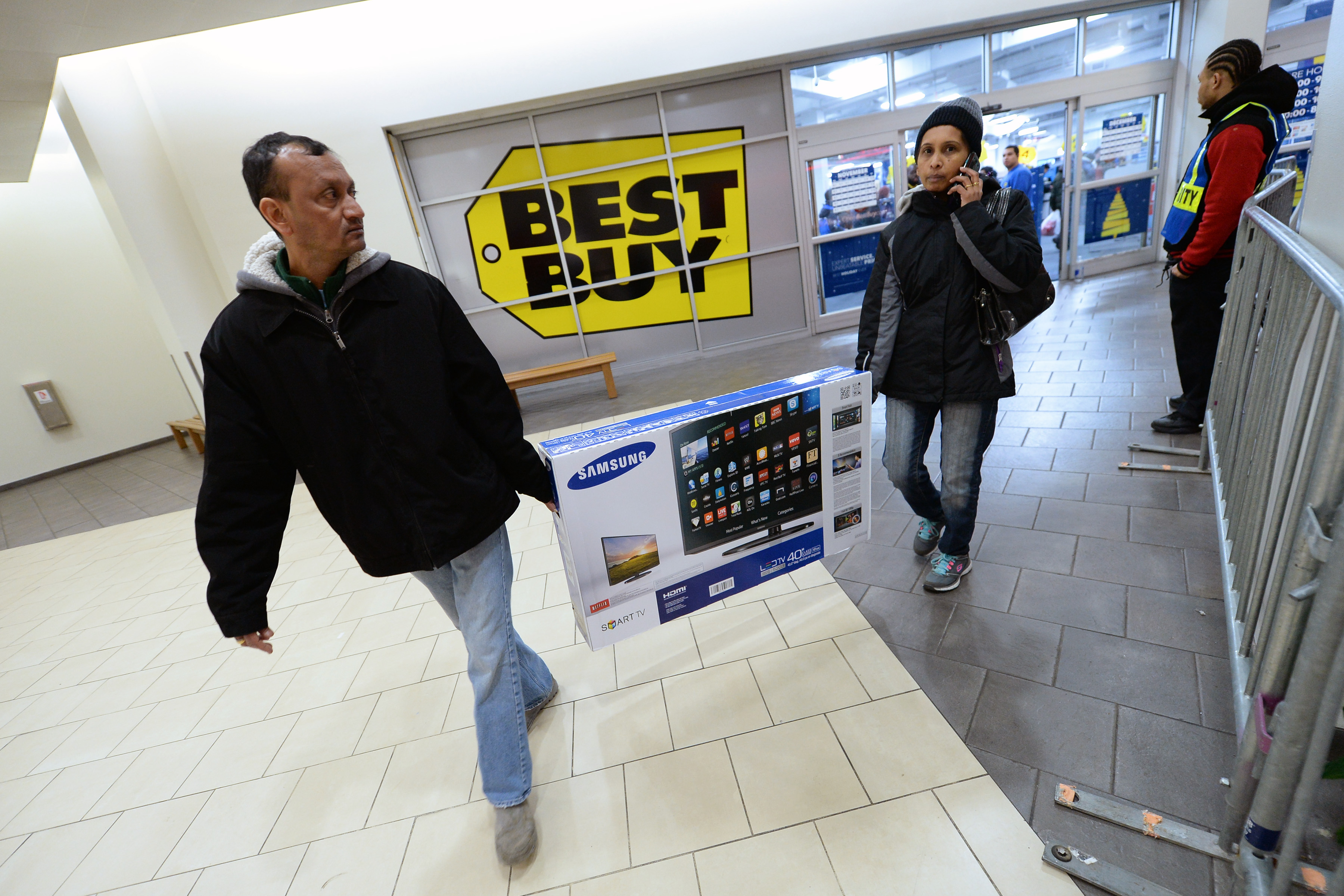 Two shoppers carry a large LCD TV as they exit a Best Buy electronics store in Queens on  Black Friday,  Nov. 28, 2014.
