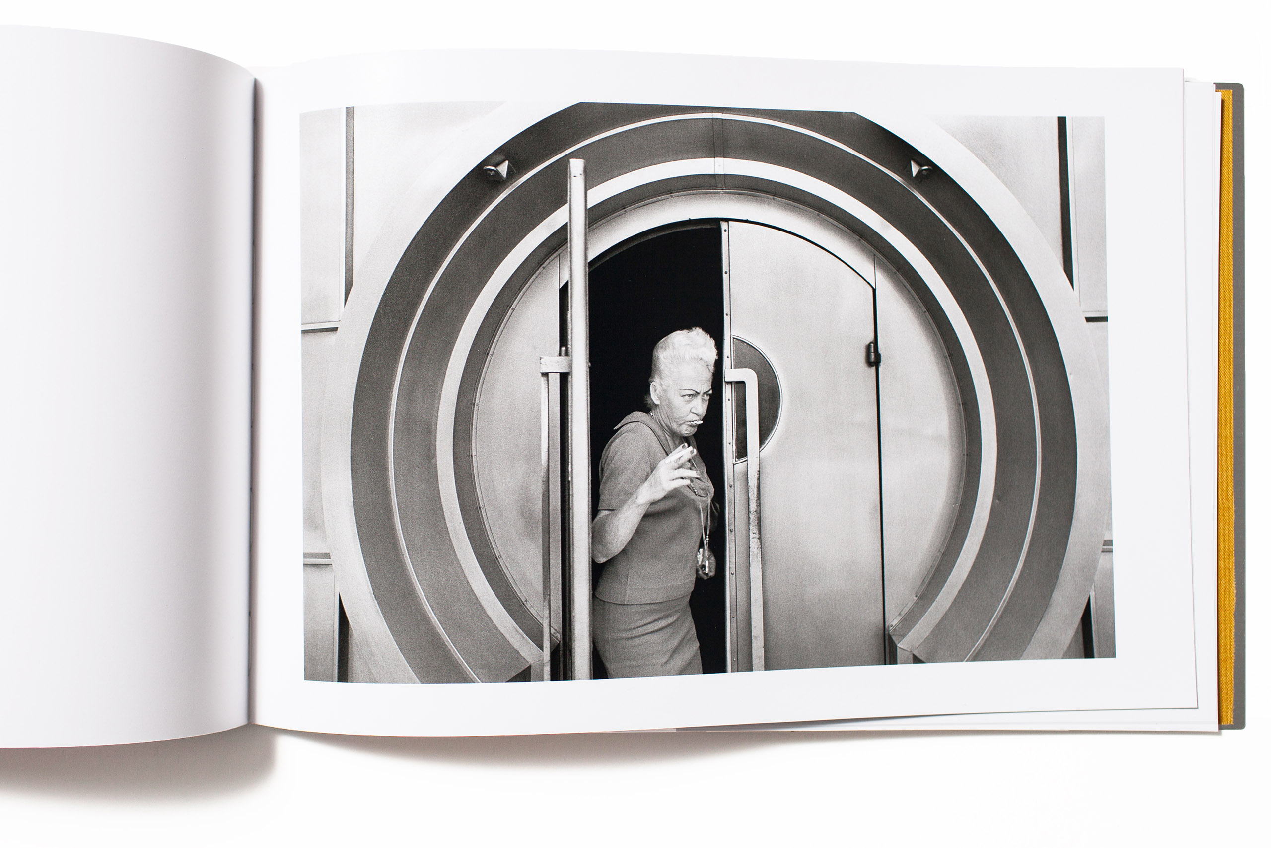 """""""How can a book comprised of twelve images of something so ordinary as people exiting a door in Los Angeles (that looks oddly at first like a bank vault) captivate interest and validate itself as a book? Anthony Hernandez's <i>LA, 1971</i> is a prime example. Is this an early work by the artist inspired and based in conceptualism or simply a string of images that share common elements and form? <i>L.A. 1971</i> is a surprising and beautiful find from The Silas Finch Foundation.""""                                                                      -Jeffery Ladd, photographer, writer and publisher of Errata Editions."""