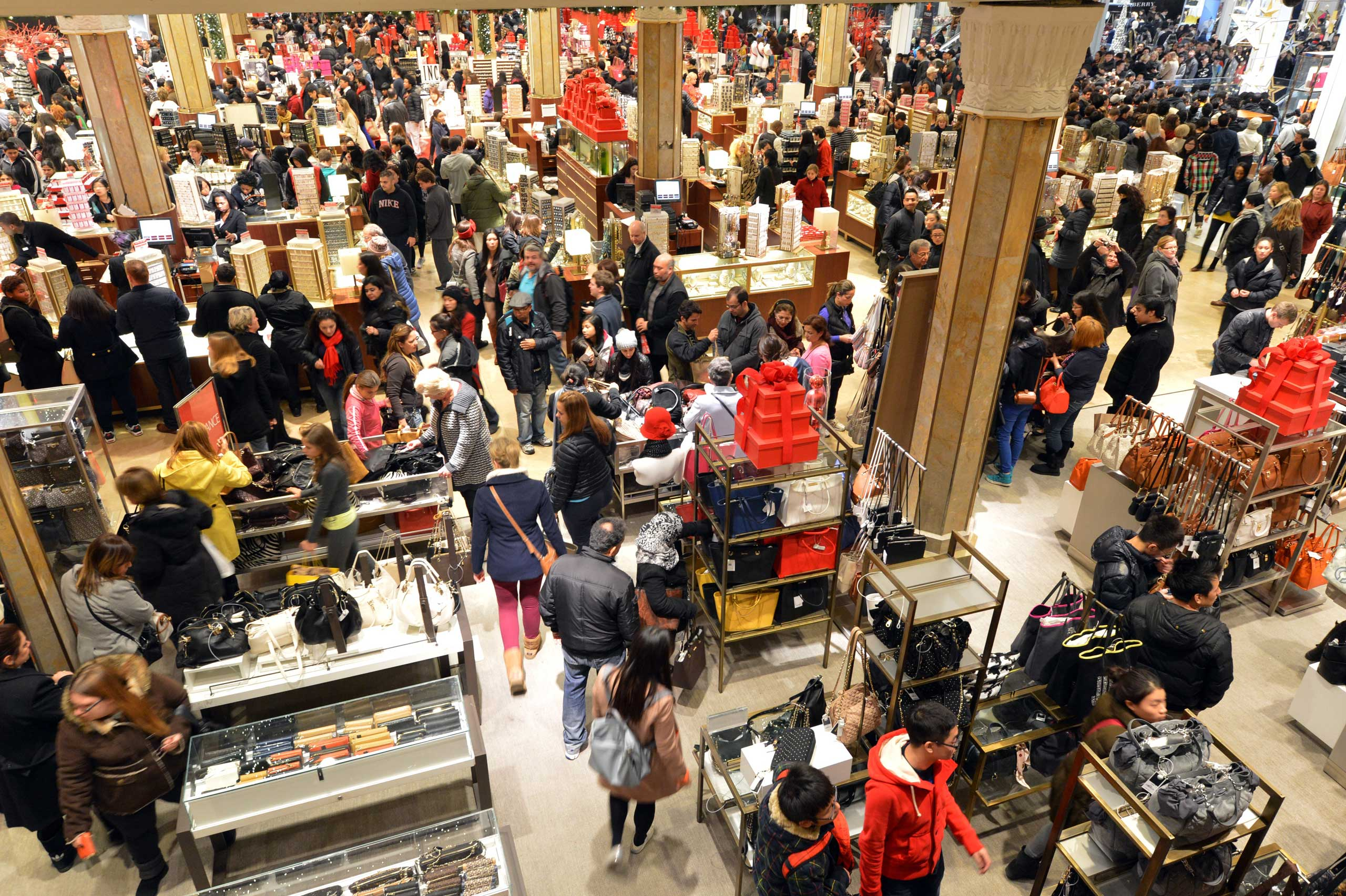 People crowd the first floor of Macy's department store as they open at midnight on Nov. 23, 2012 in New York to start the stores'  Black Friday  shopping weekend.