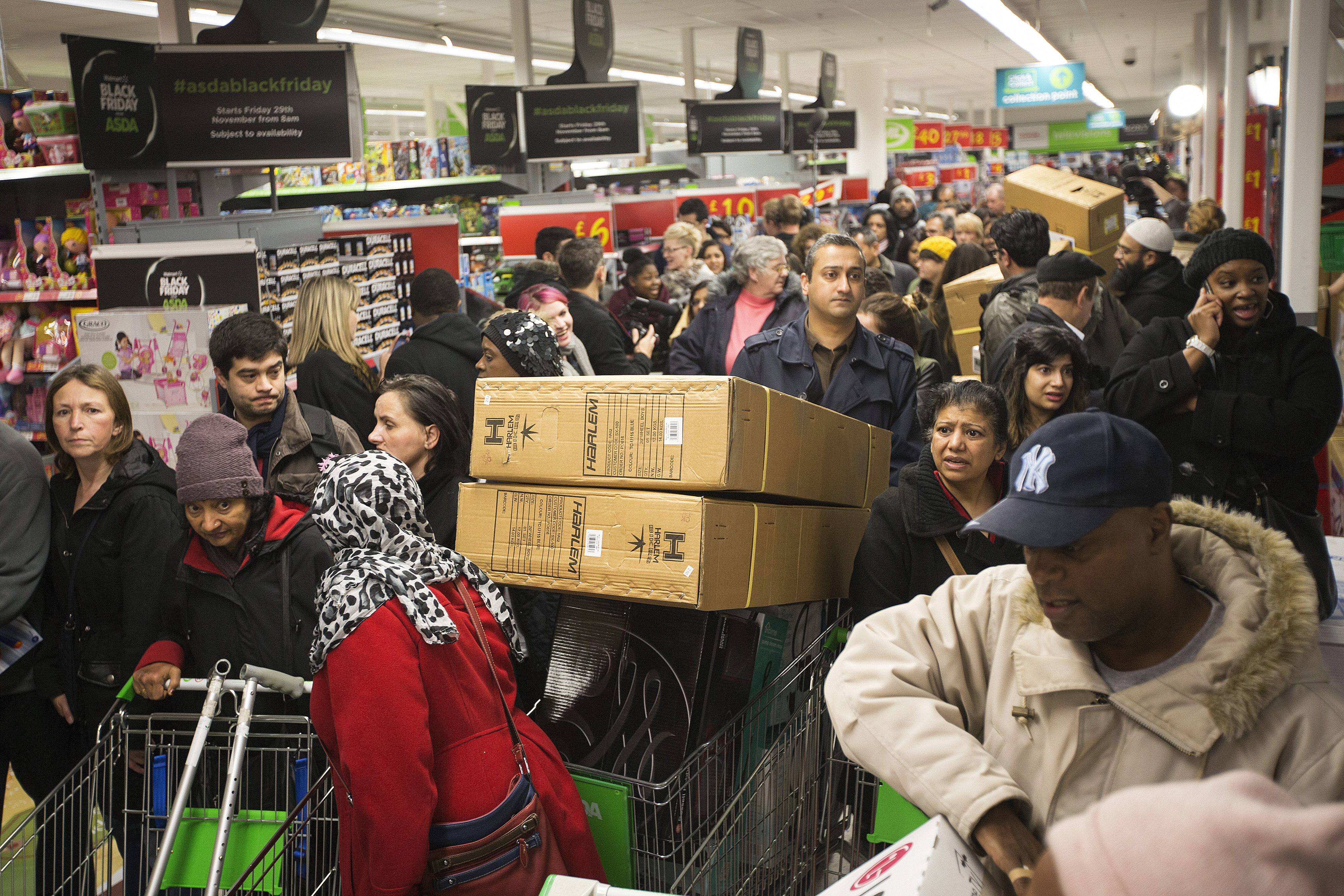 Customers push loaded shopping carts through crowded aisles as they look for bargains during a Black Friday discount sale inside an Asda supermarket in Wembley, London, U.K., on Friday, Nov. 29, 2013.