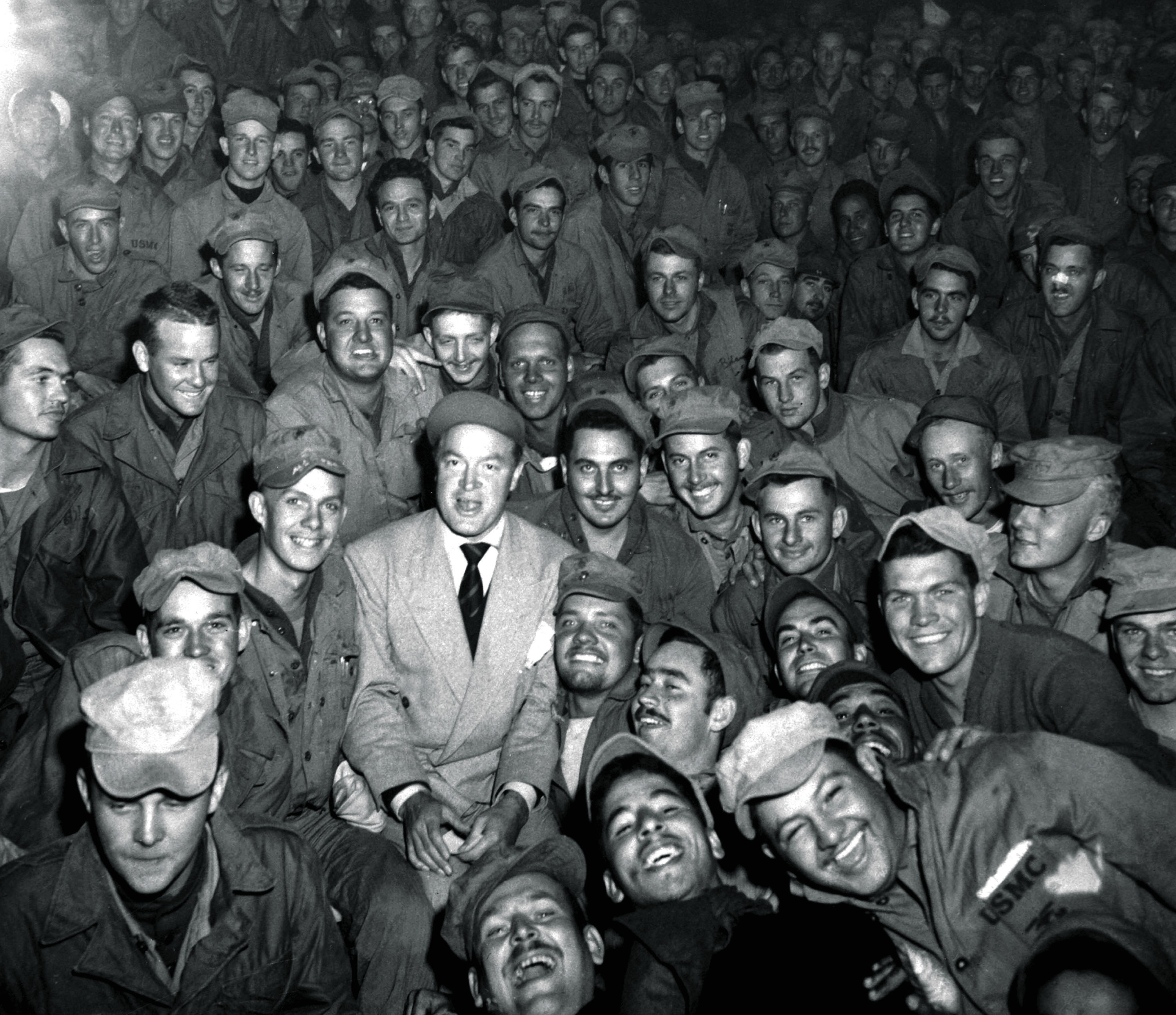 Radio and screen star Bob Hope (1903 - 2003) sits with the men of X Corps, as members of Hope's troupe entertain soldiers serving during the Korean War, in Womsan, Korea, October 1950. US Army photo. (Photo by Interim Archives/Getty Images)