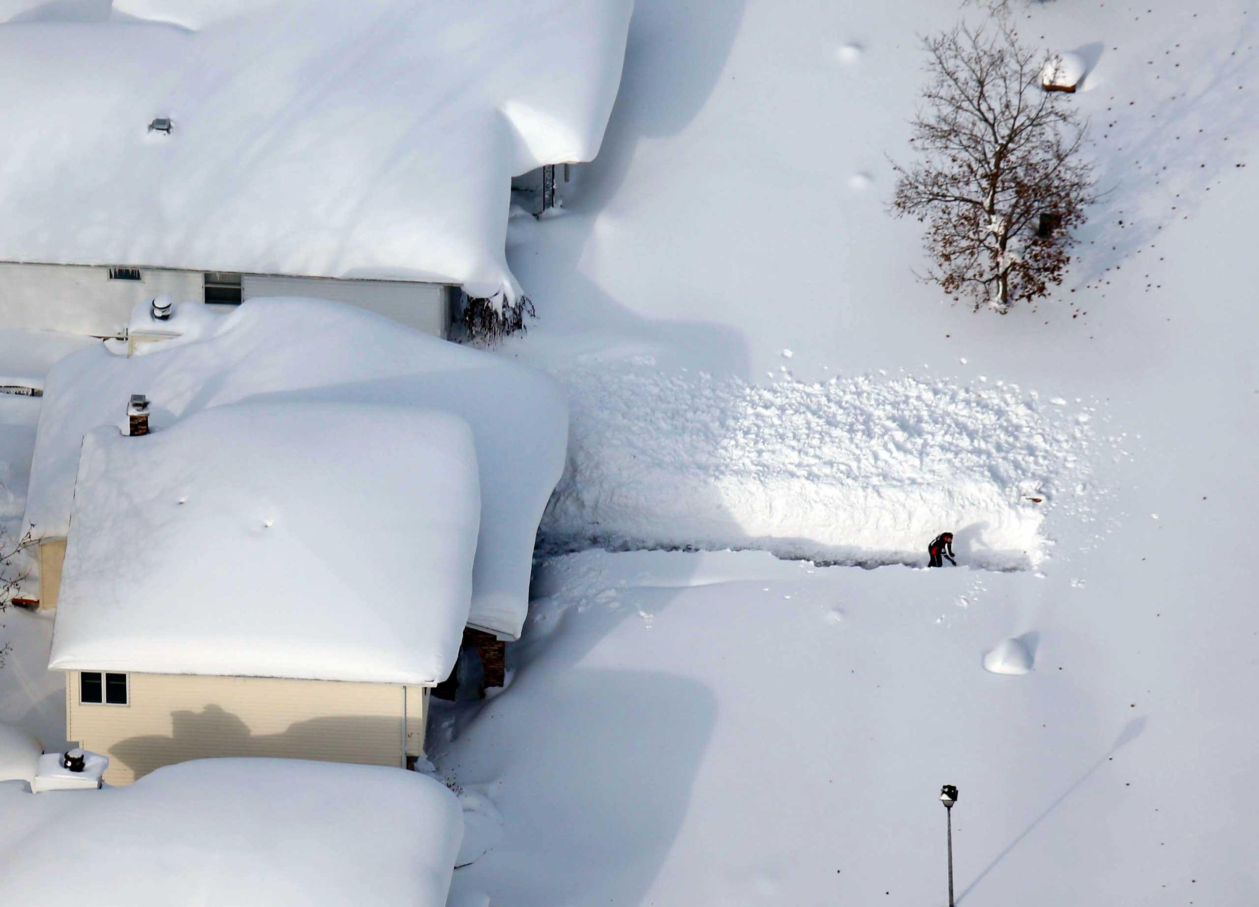 A man digs out his driveway in Depew, N.Y. on Nov. 19, 2014.