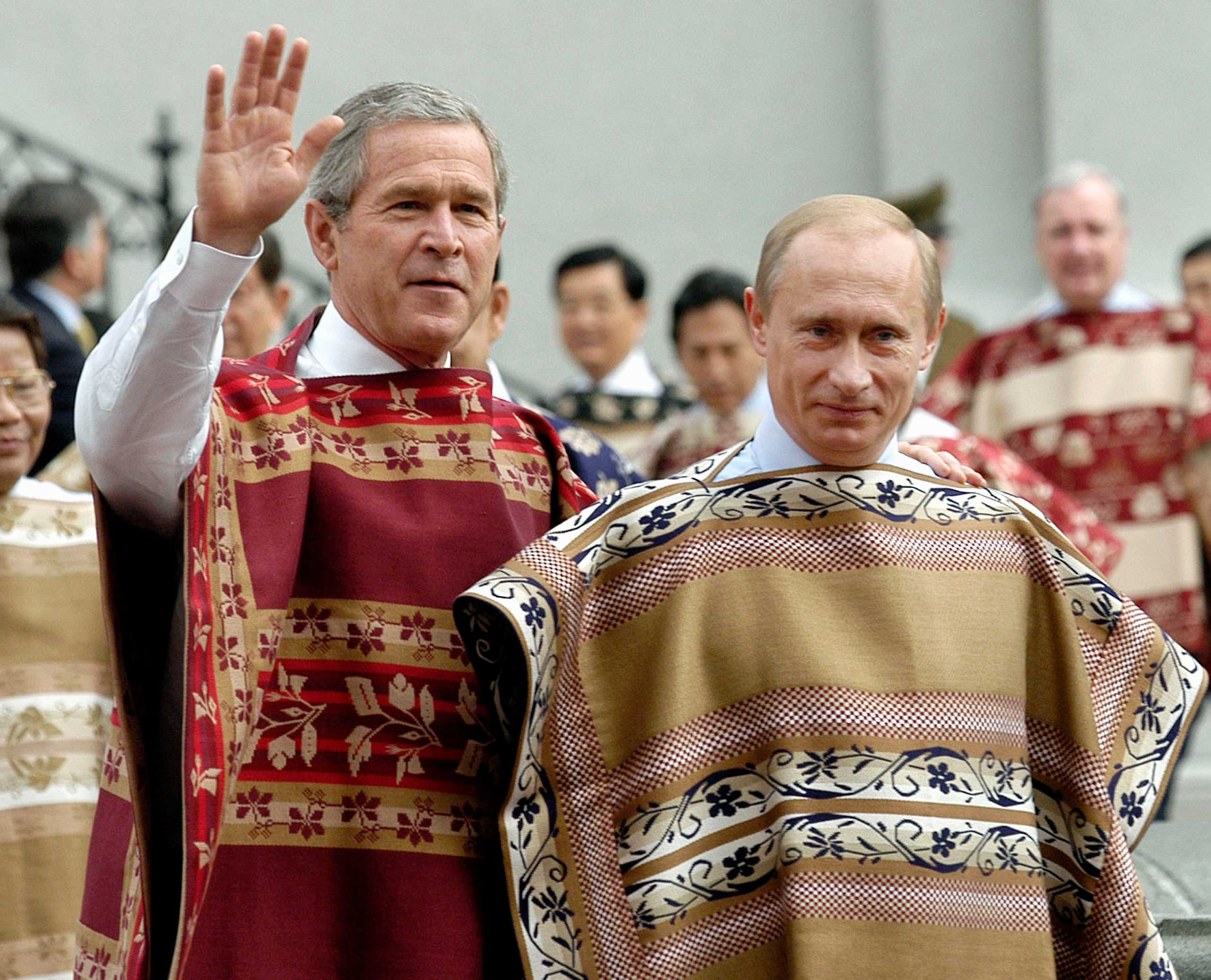 President George W. Bush, left, and Russian President Vladimir Putin, wear traditional Chilean ponchos prior to the leaders' group photo at the 2004 APEC Summit in Santiago, Chile in 2004.