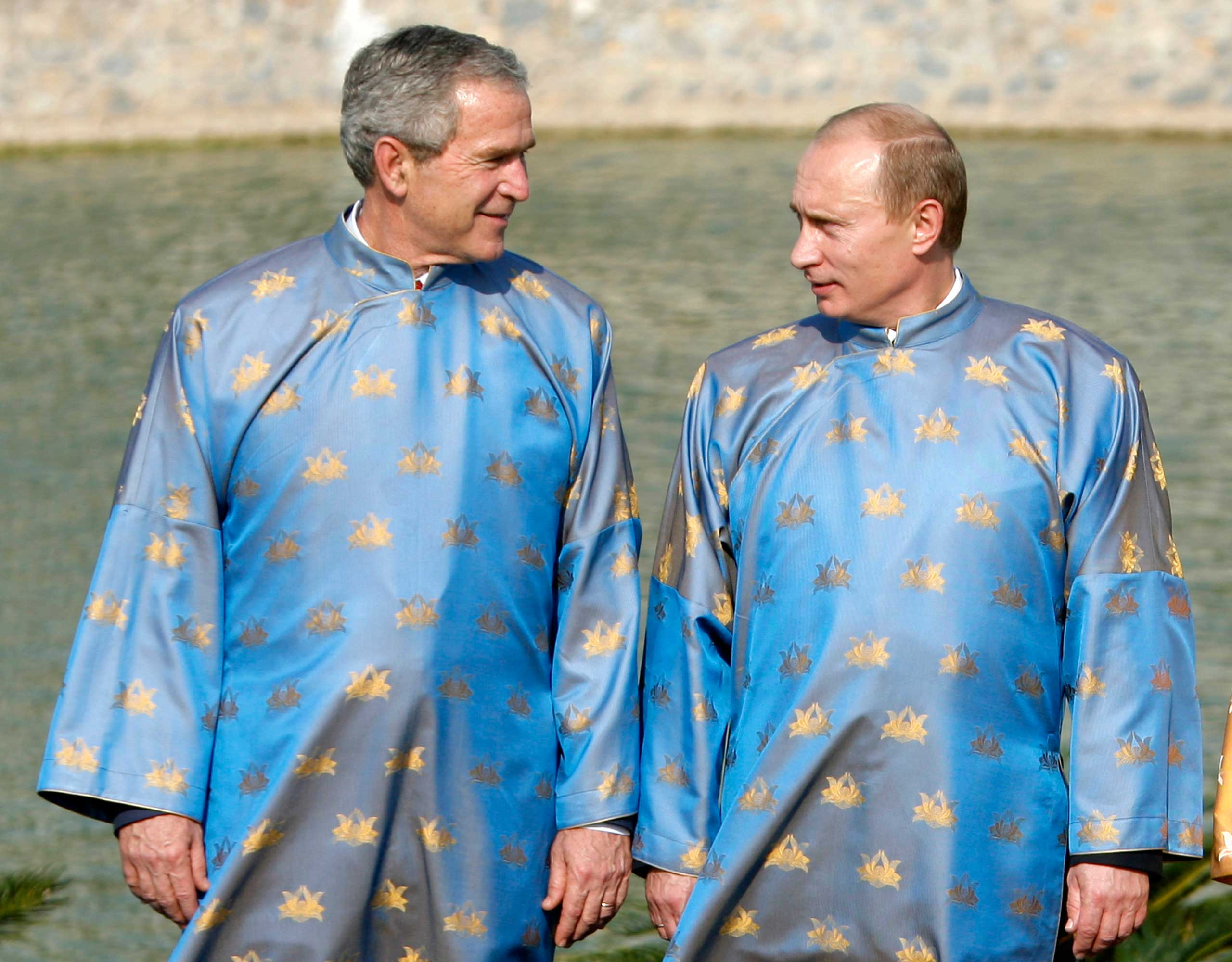President George W. Bush speaks with Russian President Vladimir Putin, wearing Vietnamese 'ao dai' silk tunics, during the official photograph for the Asia-Pacific Economic Cooperation (APEC) Summit in Hanoi. Vietnam in 2006.