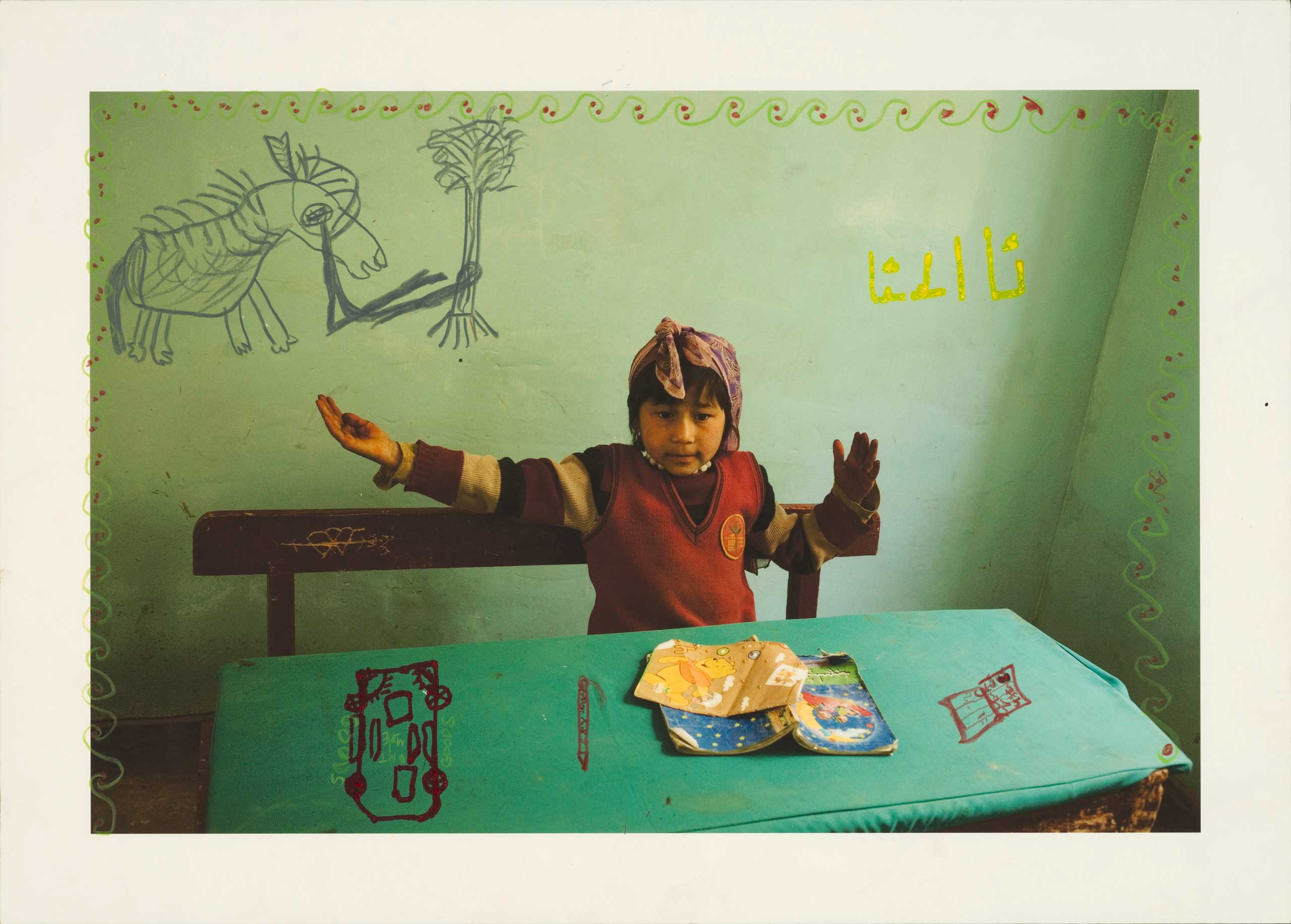 "I photographed Guliman learning the Uyghur alphabet at school and returned several years later with this print. She wrote the four versions of the Uyghur letter A on the wall behind her. Her gesture represents the ""final A."" 2011"
