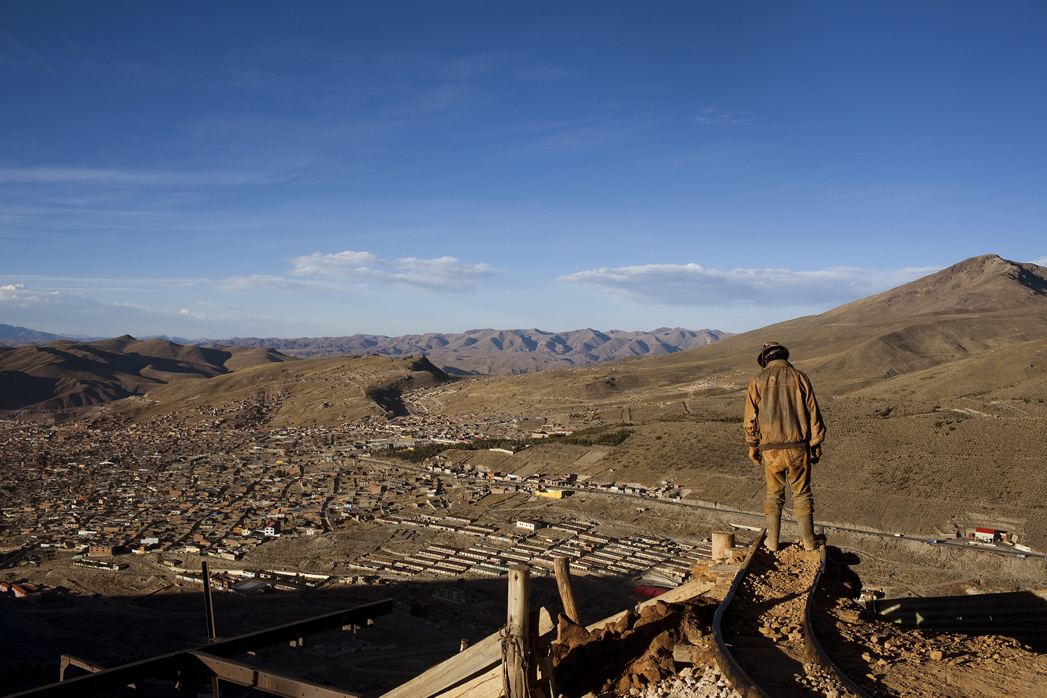 From the series: Cerro Rico  - The Mountain That Eats MenA miner stands on the edge of a mineral off-loading track outside an active mine on the mountain Cerro Rico in Potosí, Bolivia.