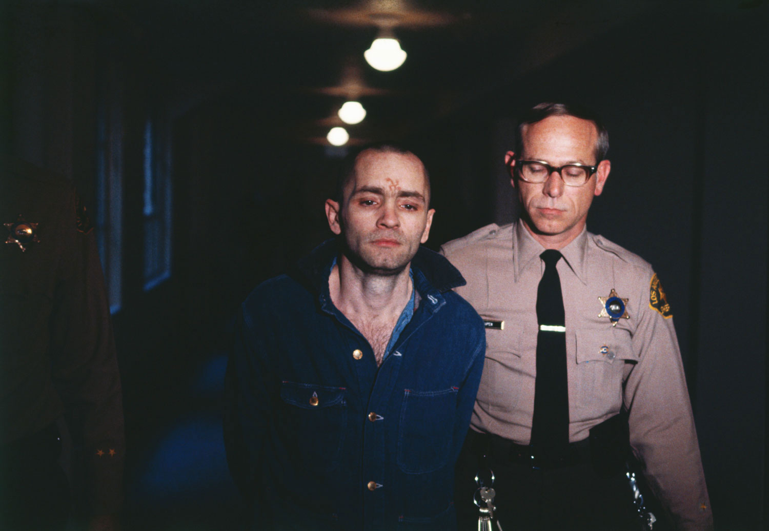 Convicted murderer Manson appears with a swastika carved into his forehead as he is led back to the courtroom to hear the penalty he and this three female followers must pay for the Tate-LaBianca murders, on March 29, 1971.
