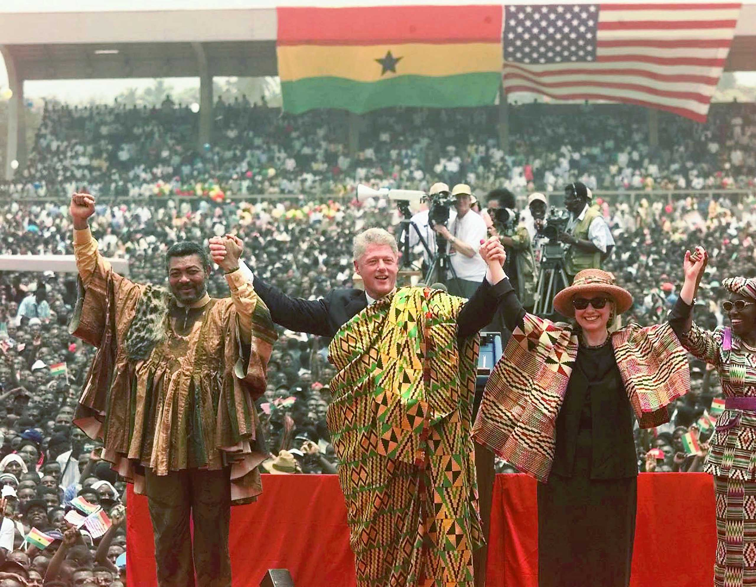 Ghana's President Jerry John Rawlings, left, President Bill Clinton, First Lady Hillary Rodham Clinton, both wearing the Kente traditional Ghanaian dress, and Ghana's First Lady Nana Rawlings, right, greet a crowd of over 200,000 people assembled in Independence Square in Accra, Ghana in 1998.