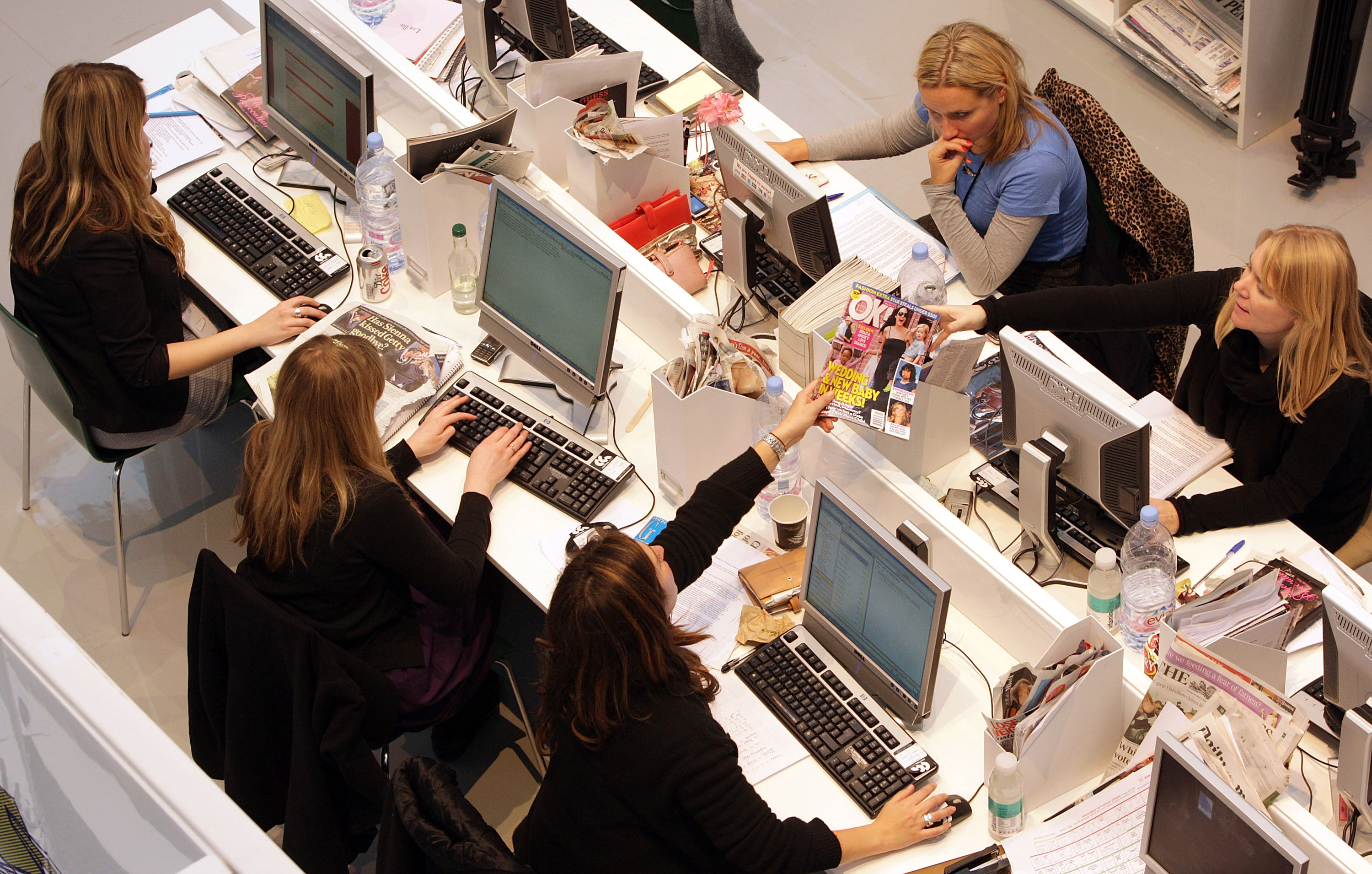 Production staff on the weekly fashion magazine, Grazia edit the magazine in a temporary office inside the Westfield shopping centre on November 3, 2008 in London.
