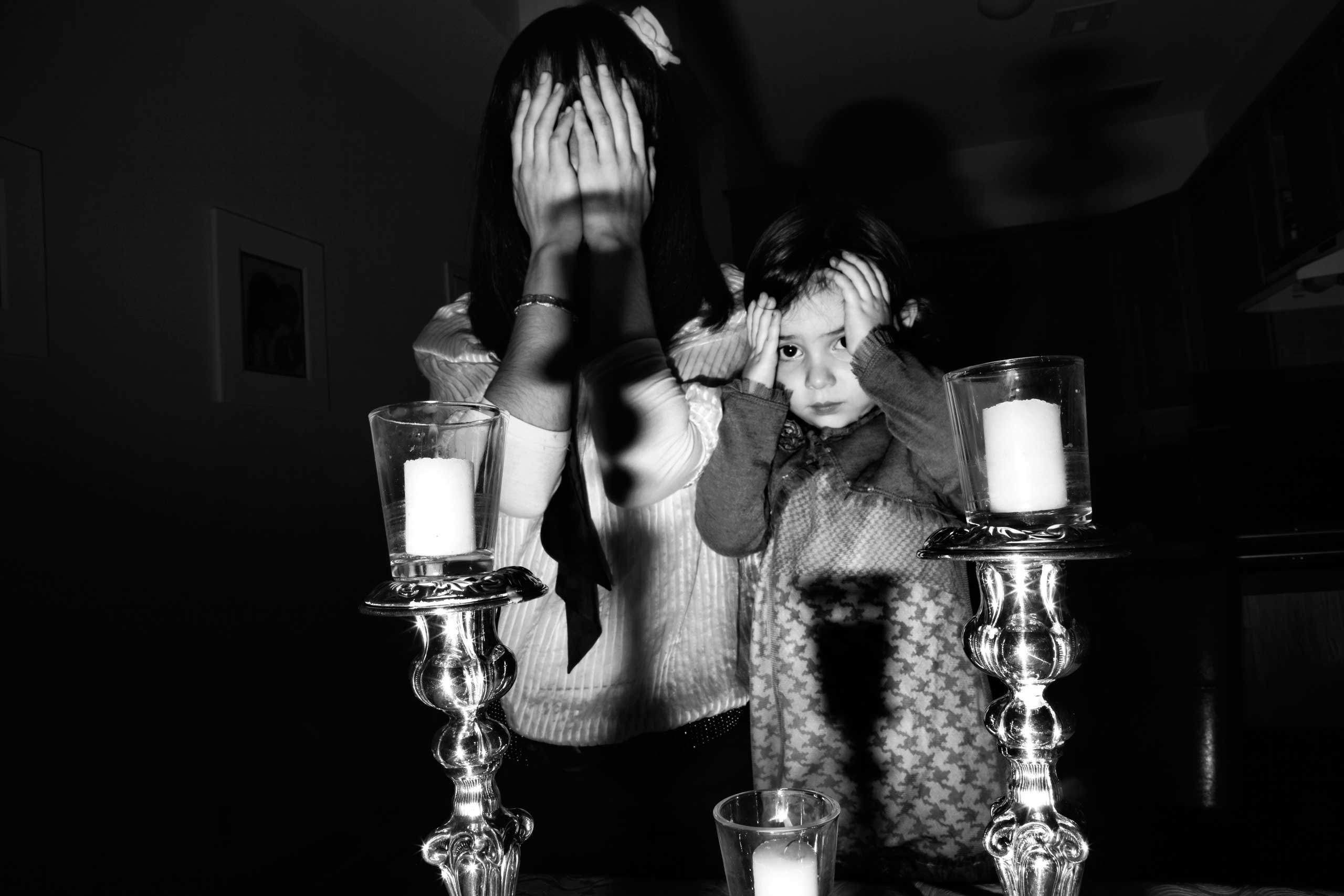 Nuchie Zirkind and her daughter, Mushka, are lighting candles to welcome the angels of Shabbat into their house before the festivities begin. Crown Heights, Brooklyn, 2010.