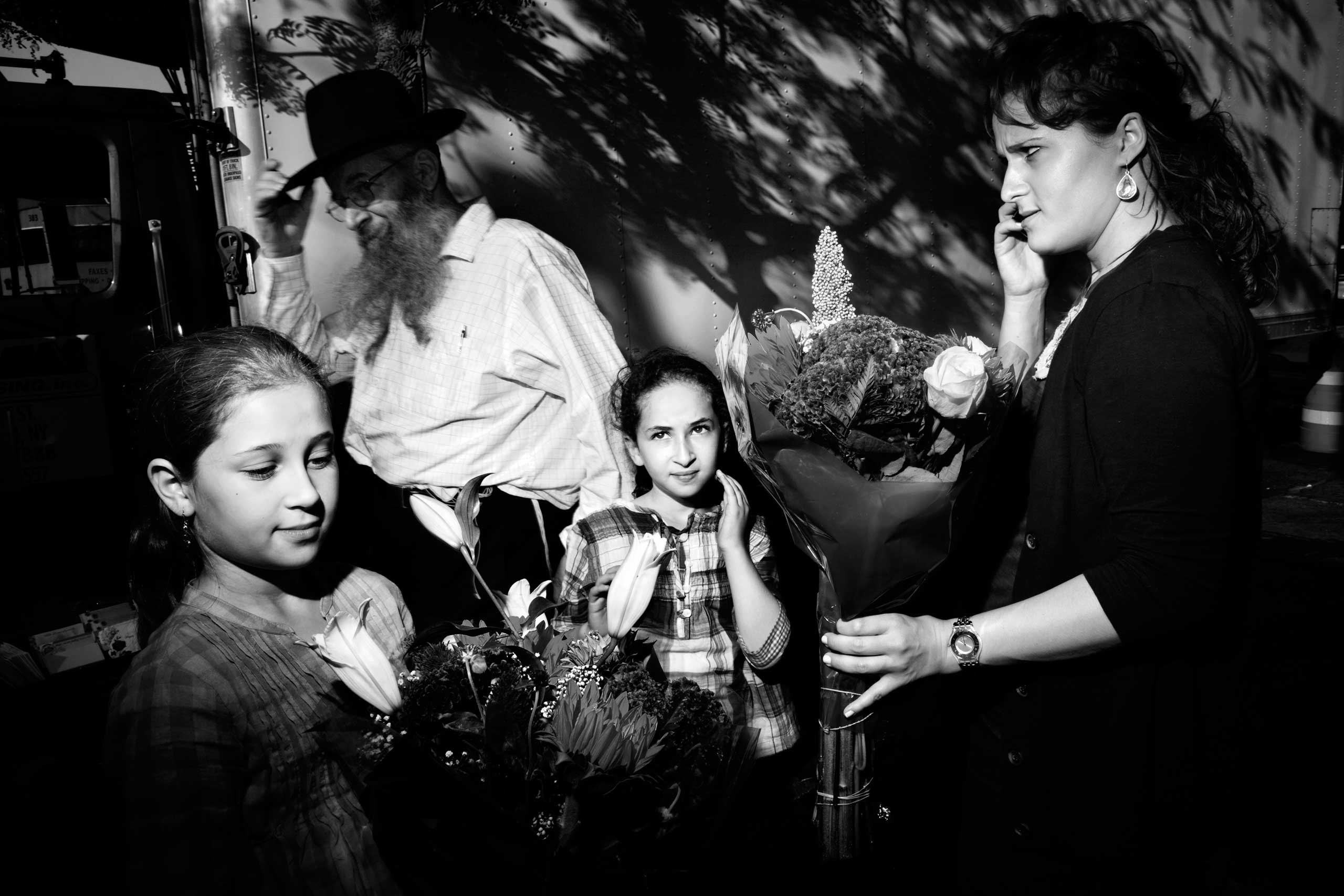 A mother and her two daughthers buys flowers before the beginning of Shabbat on Kingston Avenue, Crown Heights, Brooklyn. Oct. 2010.