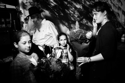 A mother and her two daughthers buys flowers before the beginning of Shabbat on Kingston Avenue, Crown Heights, Brooklyn. October 2010.