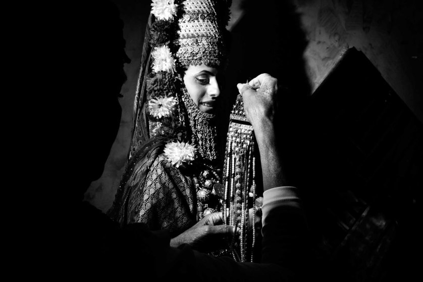 The henna is a pre-nuptial cerimony celebrated in Moroccan or Yemenite families where the soon-to-be bride is dressed-up as a Queen with flowers and jewels and she is inivited to dance with her girl friends to say good-bye to celibacy and life as a single young girl. During the dance cerimony, the Kallah, the bride-to-be's hands and feet are painted with henne`, the red pouder from India. This welcomes fertility and happinesses within the marriage. Meah Shearim, Jerusalem, Israel. July 2012.