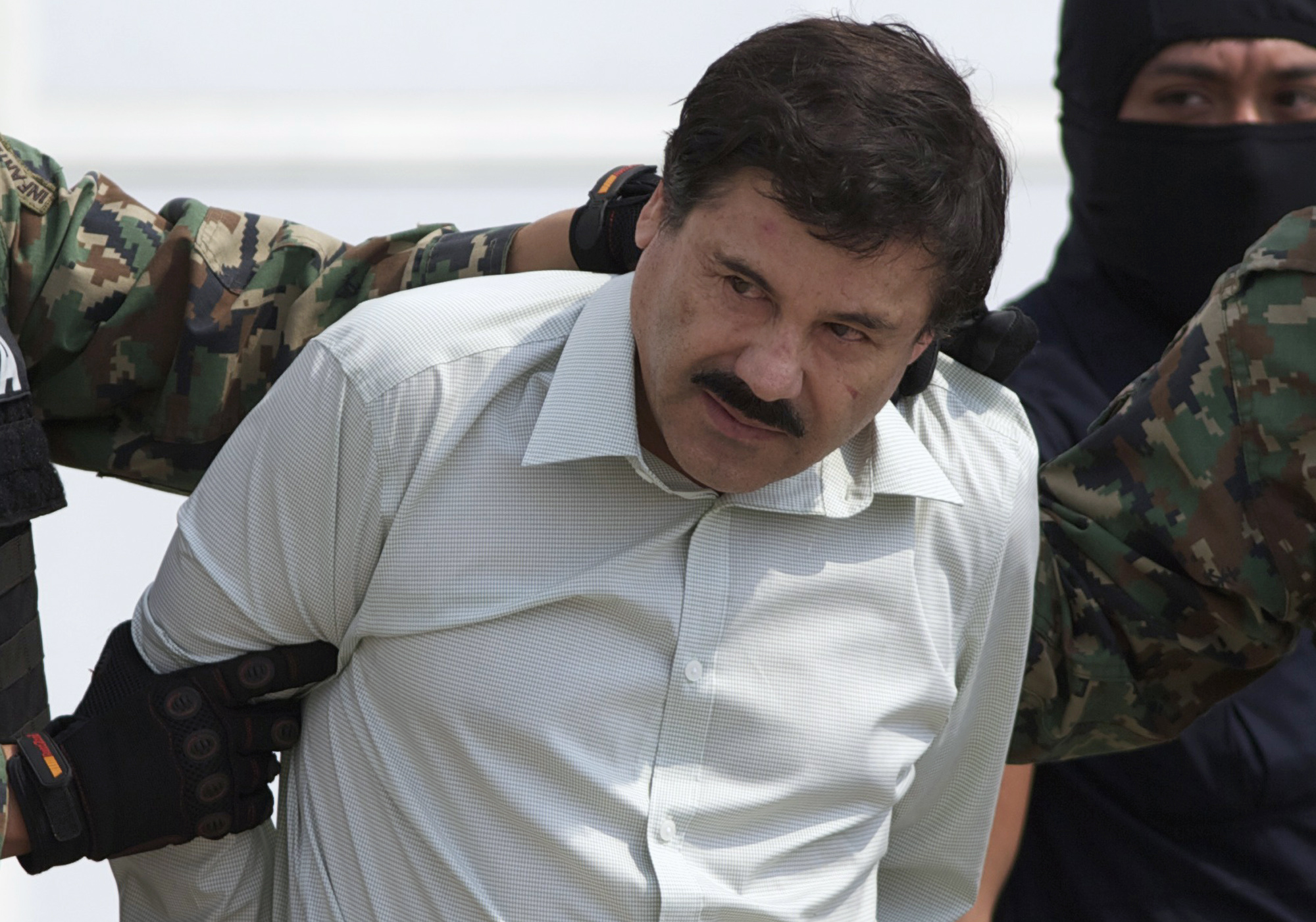 This Feb. 22, 2014, file photo shows Joaquin  El Chapo  Guzman, the head of Mexico's Sinaloa Cartel, being escorted to a helicopter in Mexico City following his capture overnight in the beach resort town of Mazatlan