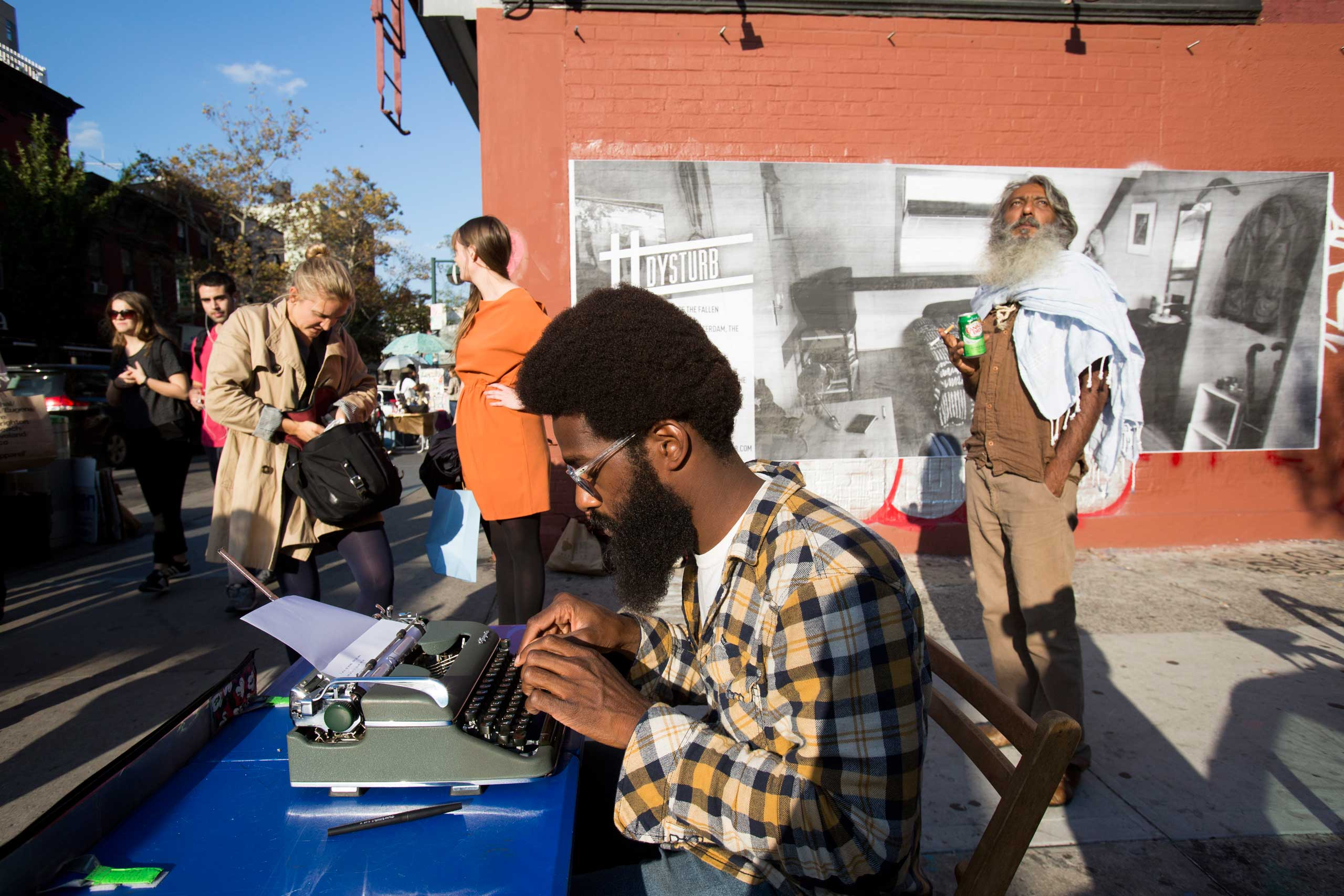 Passersby in Brooklyn, New York in front of one of Dysturb's photographs (on the corner of N 6th Street and Bedford Avenue). October 17th 2014.