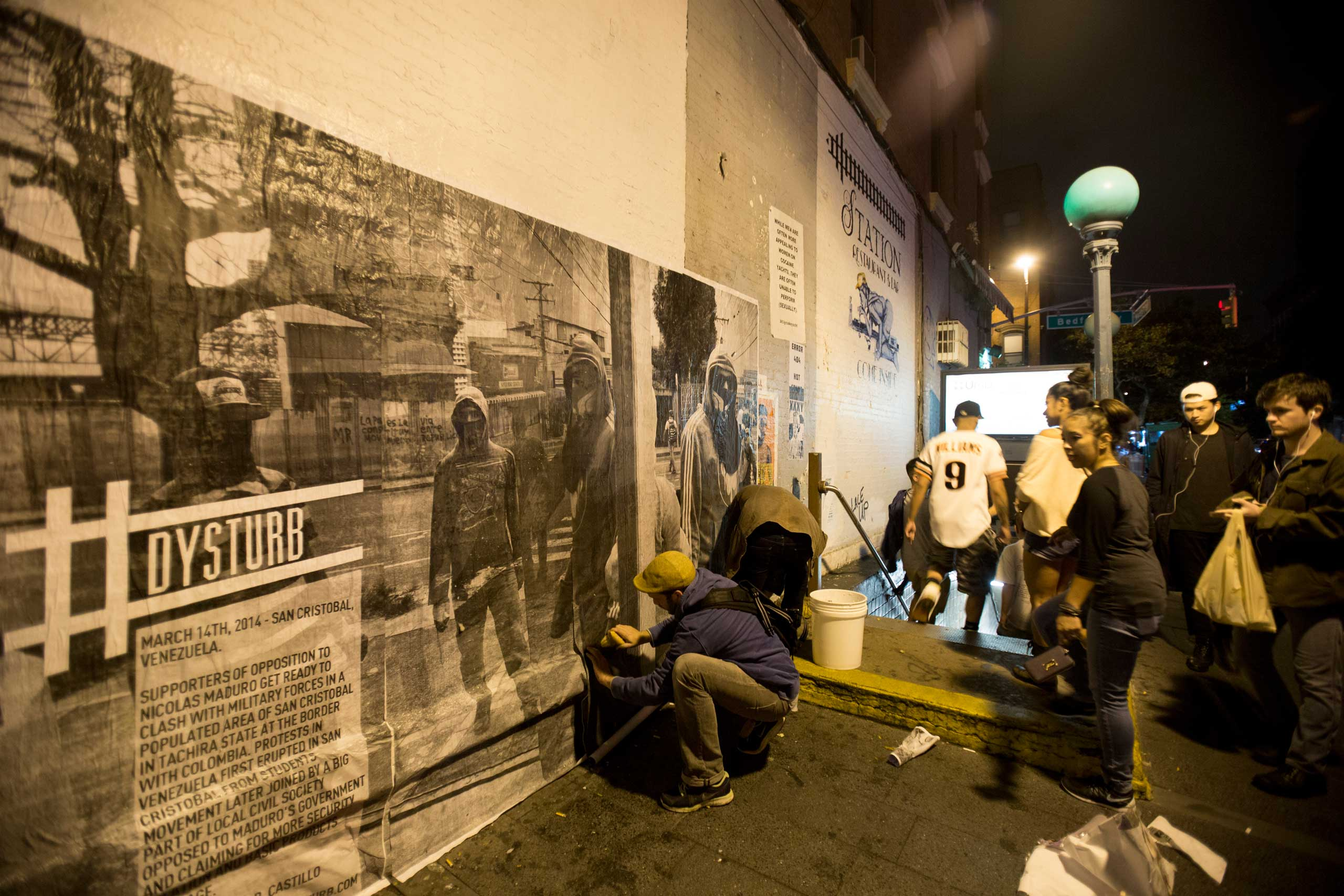 Onlookers, as the Dysturb team paste a photograph in Brooklyn, New York (on the corner of N 7th Street and Bedford Avenue). October 16th 2014.