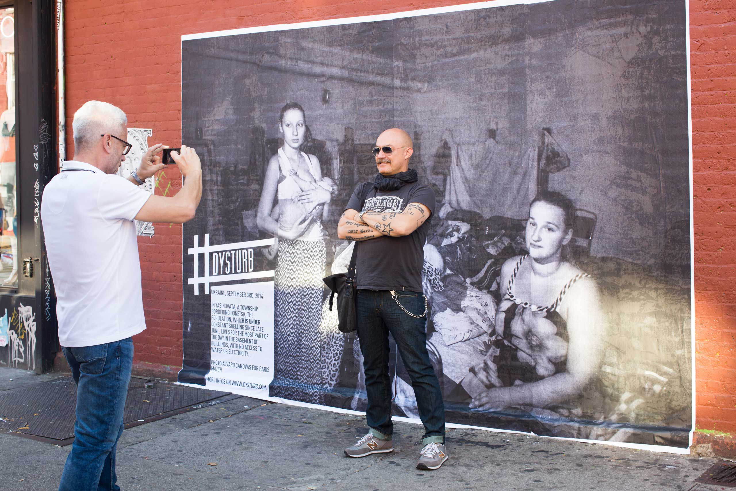 A New Yorker in front of one of Dysturb's photographs (in Brooklyn, on the corner of N 6th Street and Bedford Avenue). October 17th 2014.