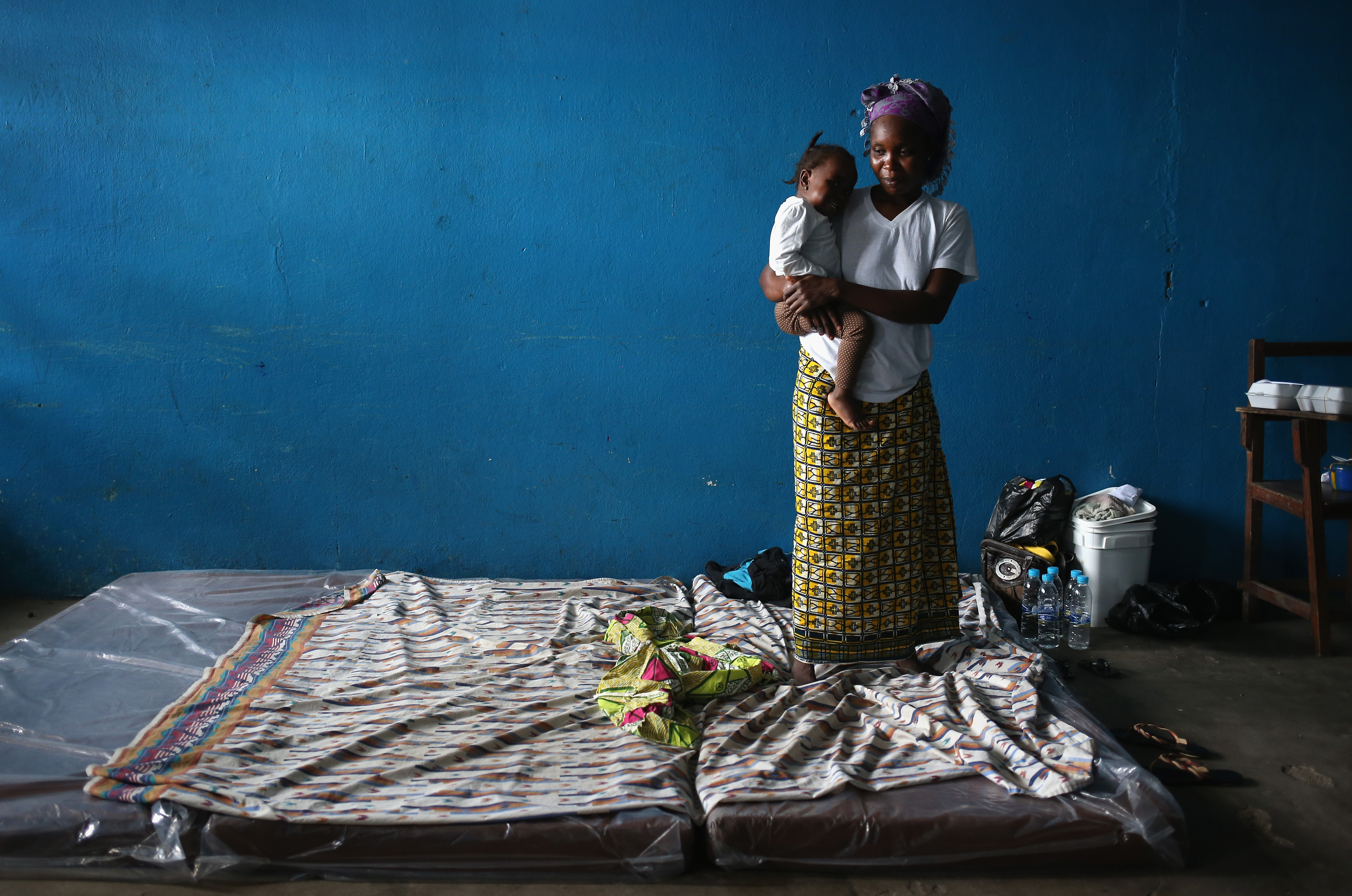 A mother and child stand atop their mattresses in a classroom now used as Ebola isolation ward on Aug. 15, 2014, in Monrovia, Liberia