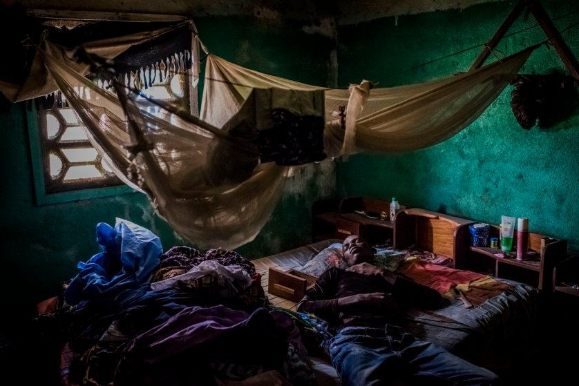 Mark Jerry, who along with his adopted daughter was turned away from an Ebola clinic a day prior, rests at his grandmother?s home in Monrovia, Liberia.