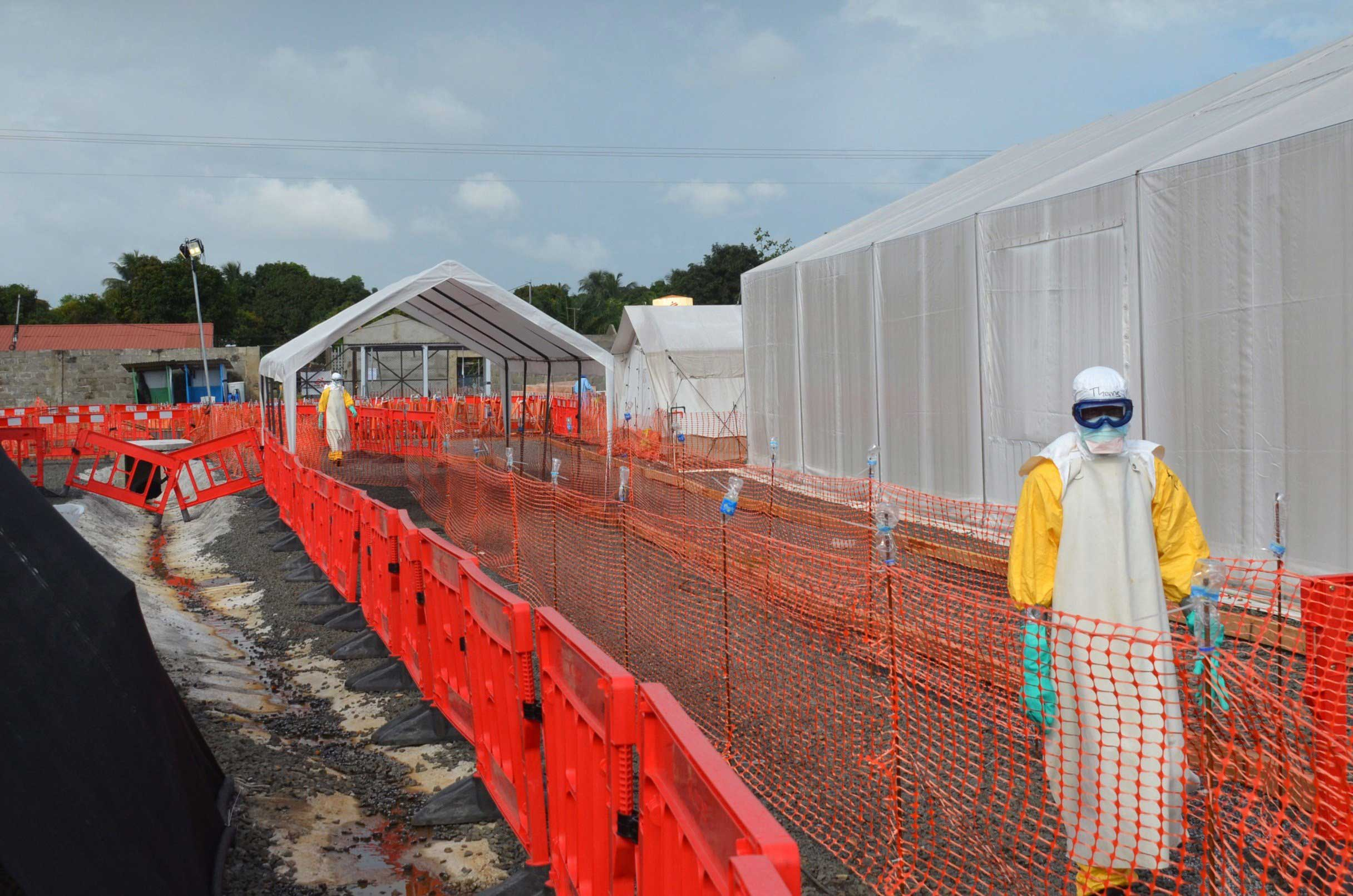 Health workers wearing Personal Protective Equipments (PPE) stand outside an Ebola treatment center run by Medecins Sans Frontieres (Doctors without Borders -- MSF) in Monrovia, Liberia on Oct. 27, 2014.