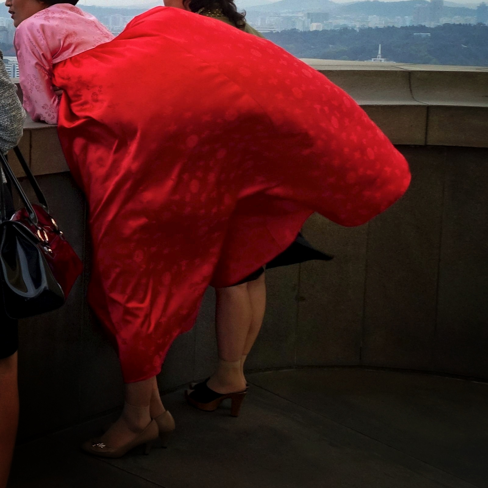 A woman's traditional dress billows in the strong breeze on top of Juche Tower in Pyongyang.