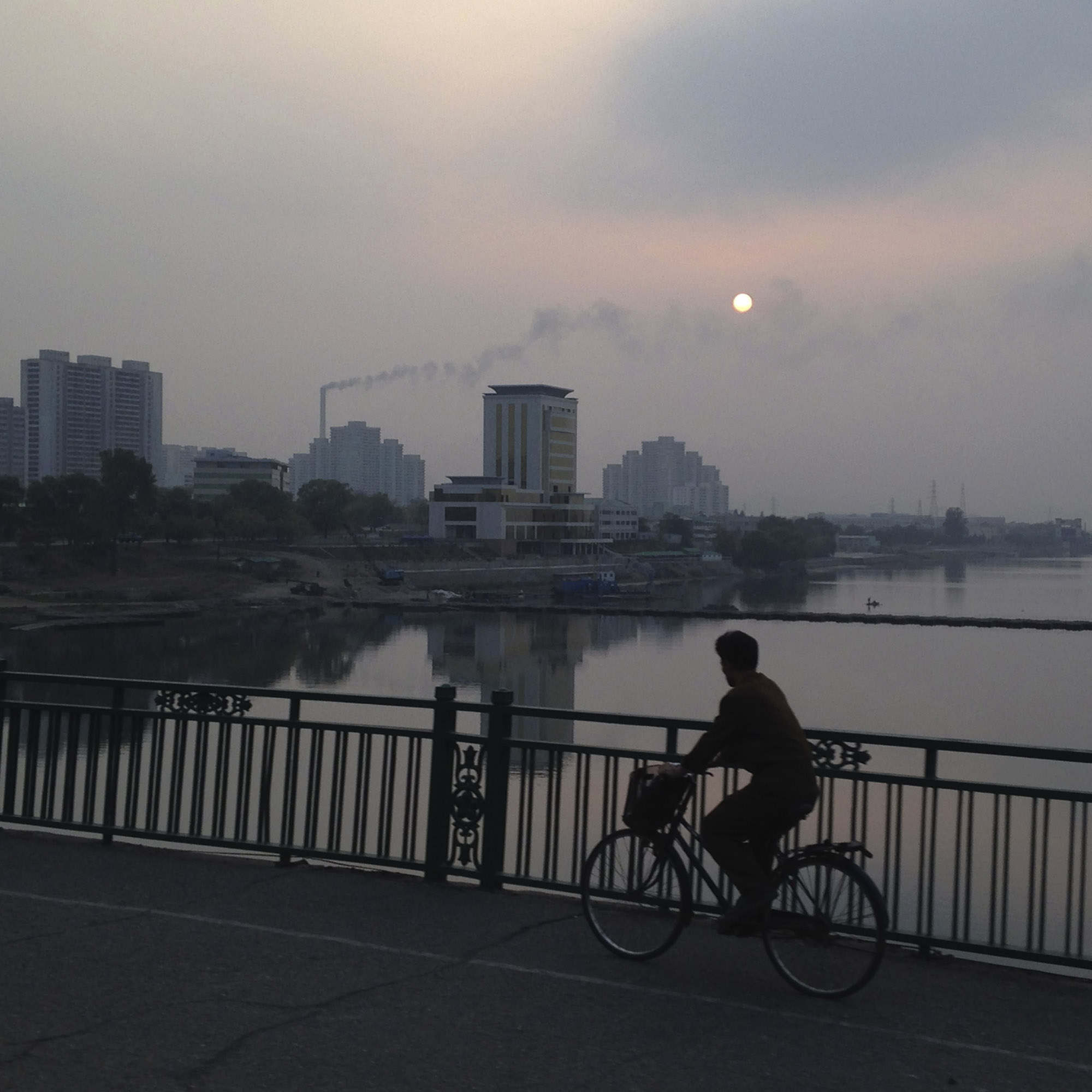 A North Korean man rides his bicycle as the sun sets over the Taedong River in Pyongyang.