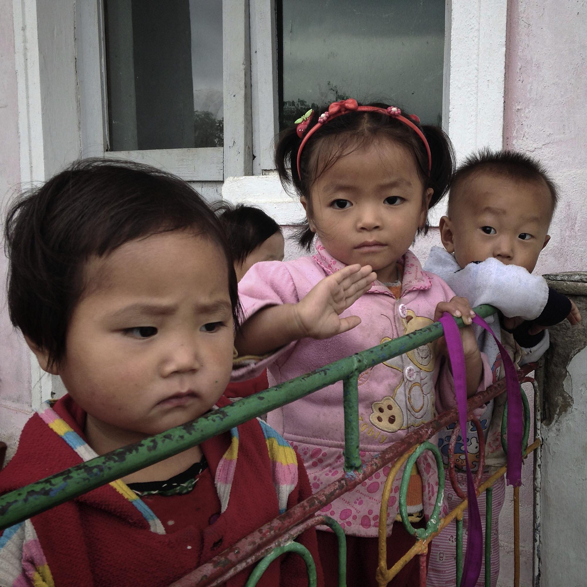 North Korean kindergarten students stand outside a school at a collective farm near Wonsan, North Korea.