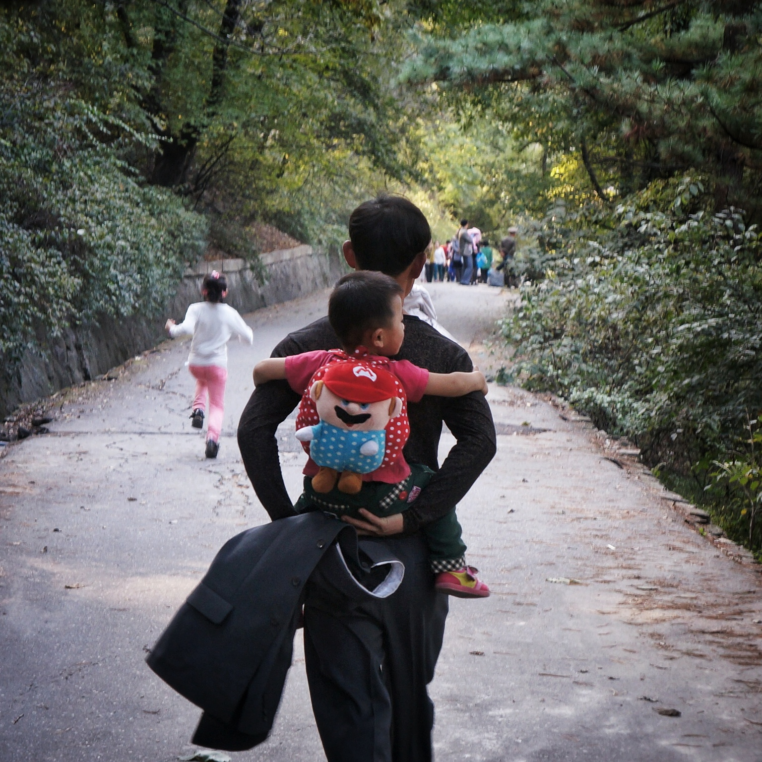 A man carries his son wearing a Mario Bros backpack in Pyongyang, North Korea.