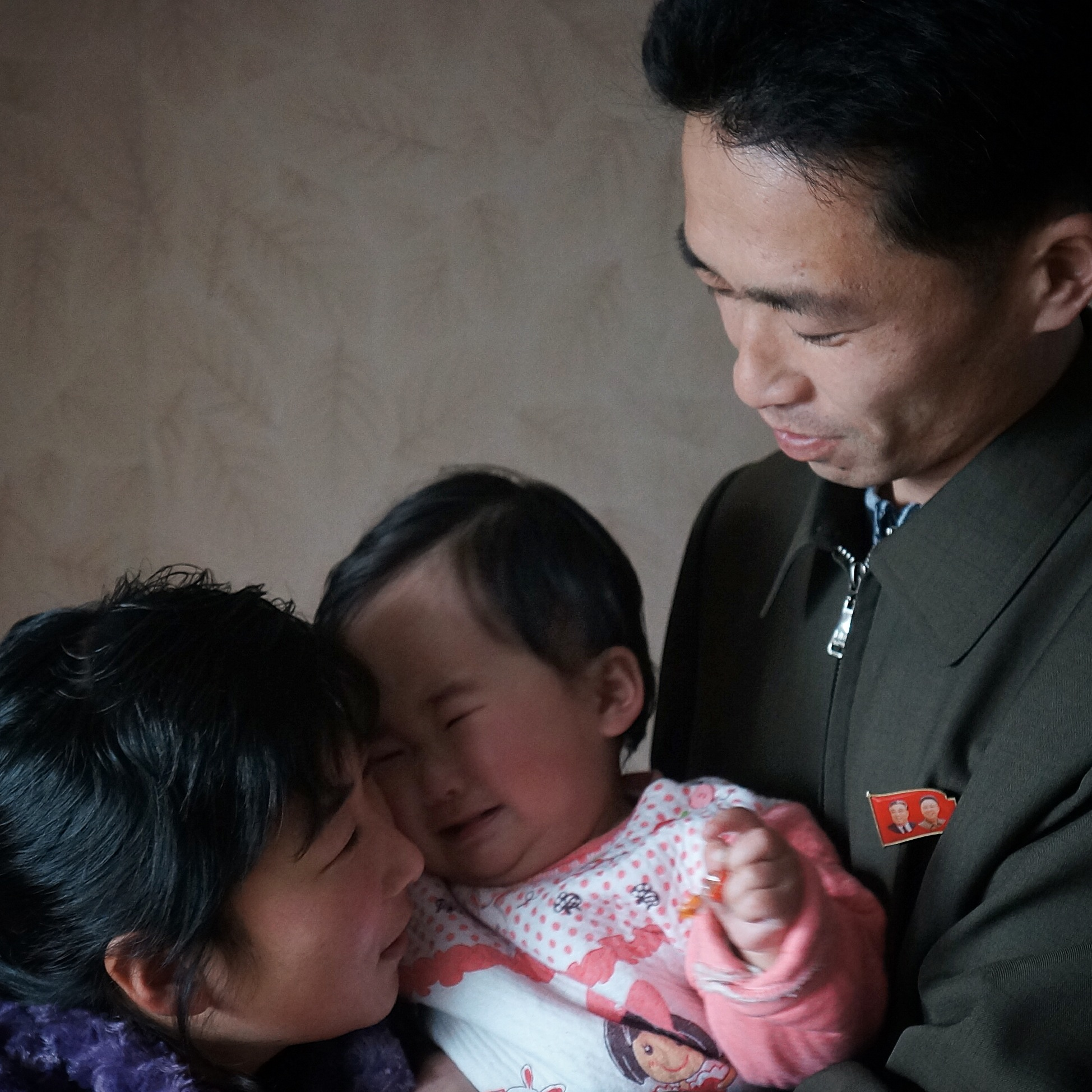 A newlywed North Korean couple comfort their crying baby in their Pyongyang home.