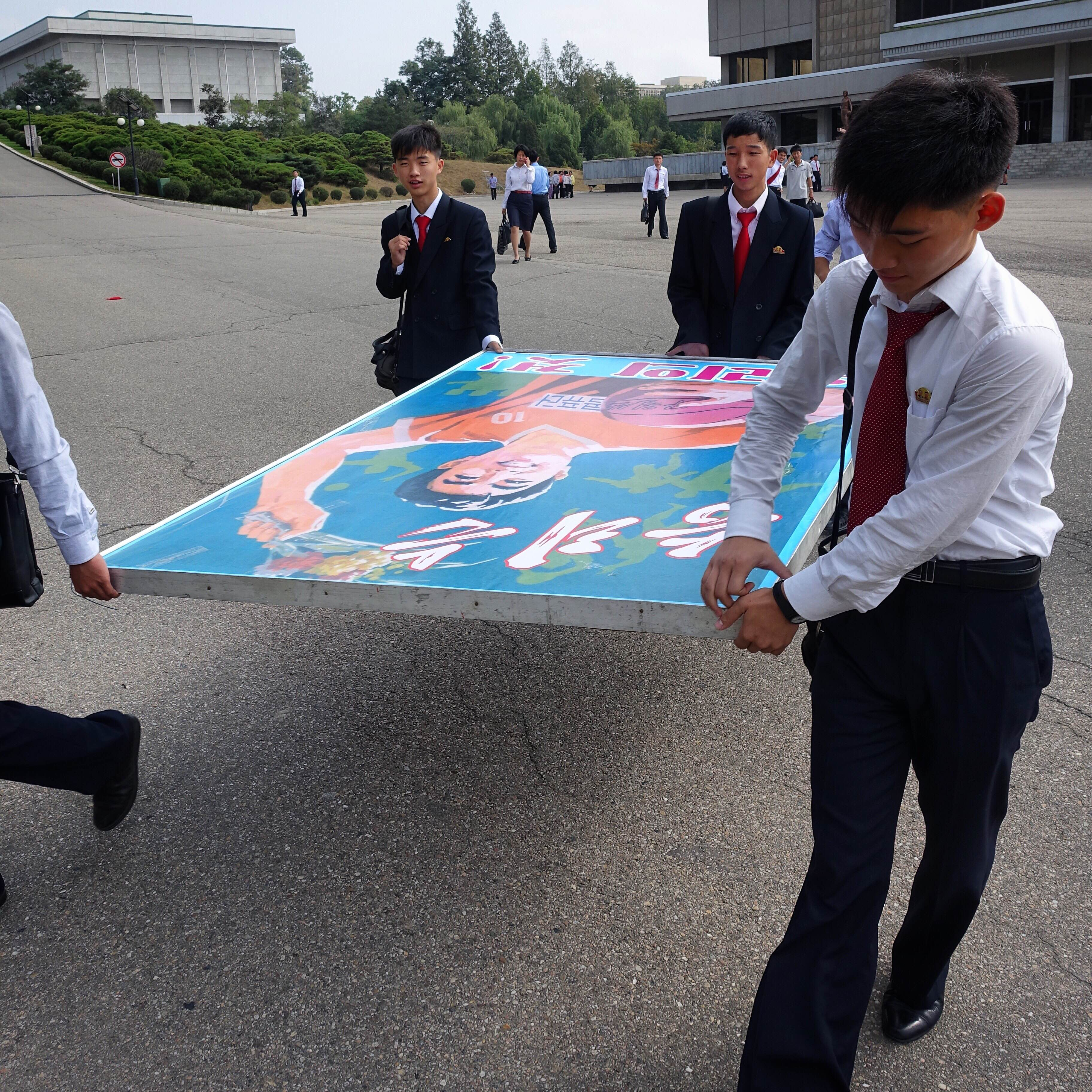 Computer Science students of Kim Il Sung University carry a poster board that says  Victory is Ours!  during the school's 78th anniversary celebrations.