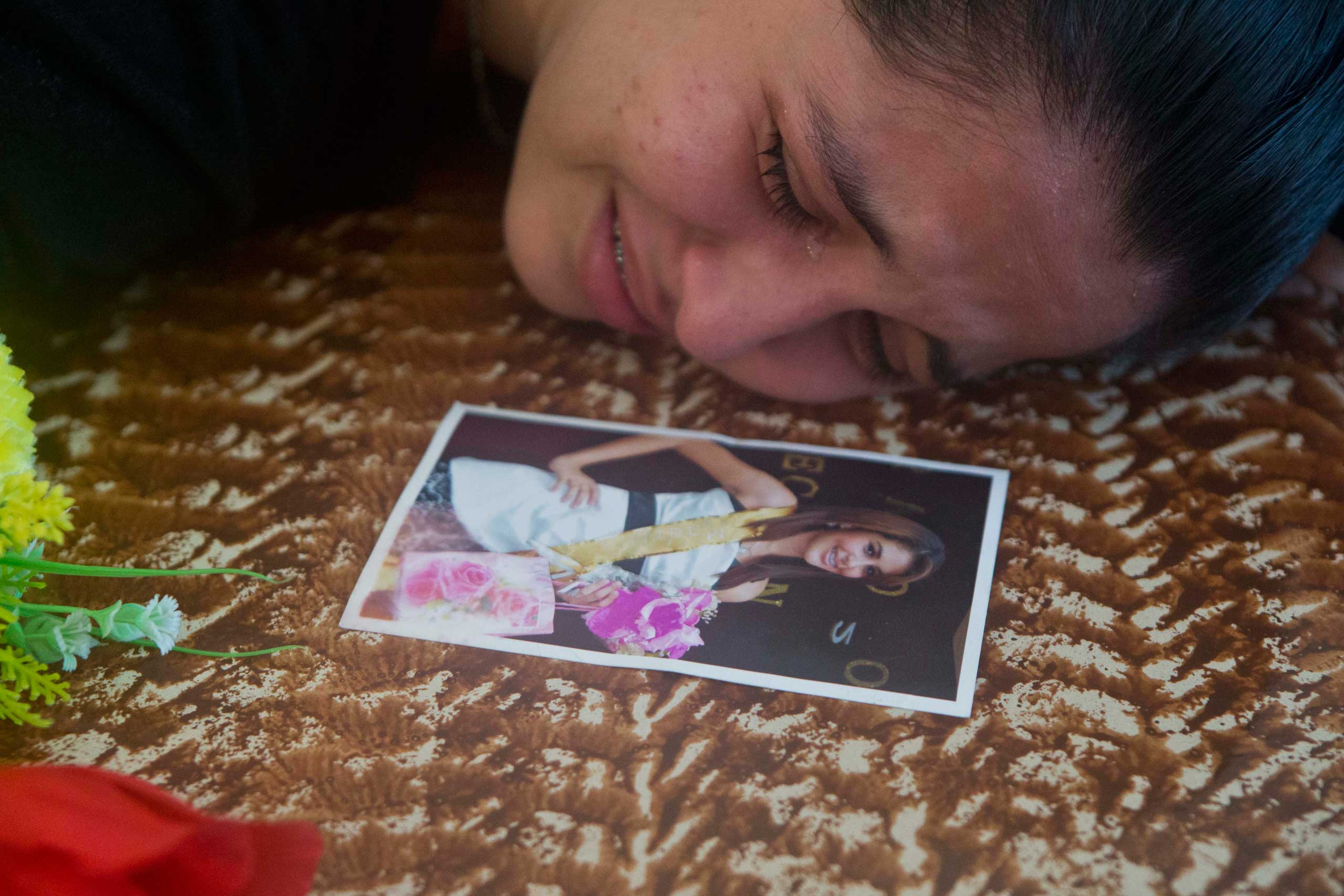 Nov. 20, 2014. Keyling Enamorado, a friend of slain beauty queen Maria Jose Alvarado, cries on Maria's coffin in Santa Barbara, Honduras. Grieving family members laid to rest the Honduran beauty queen and her sister, Sofia, after the women were shot to death in what police say was a jealous rage by the sister's boyfriend.