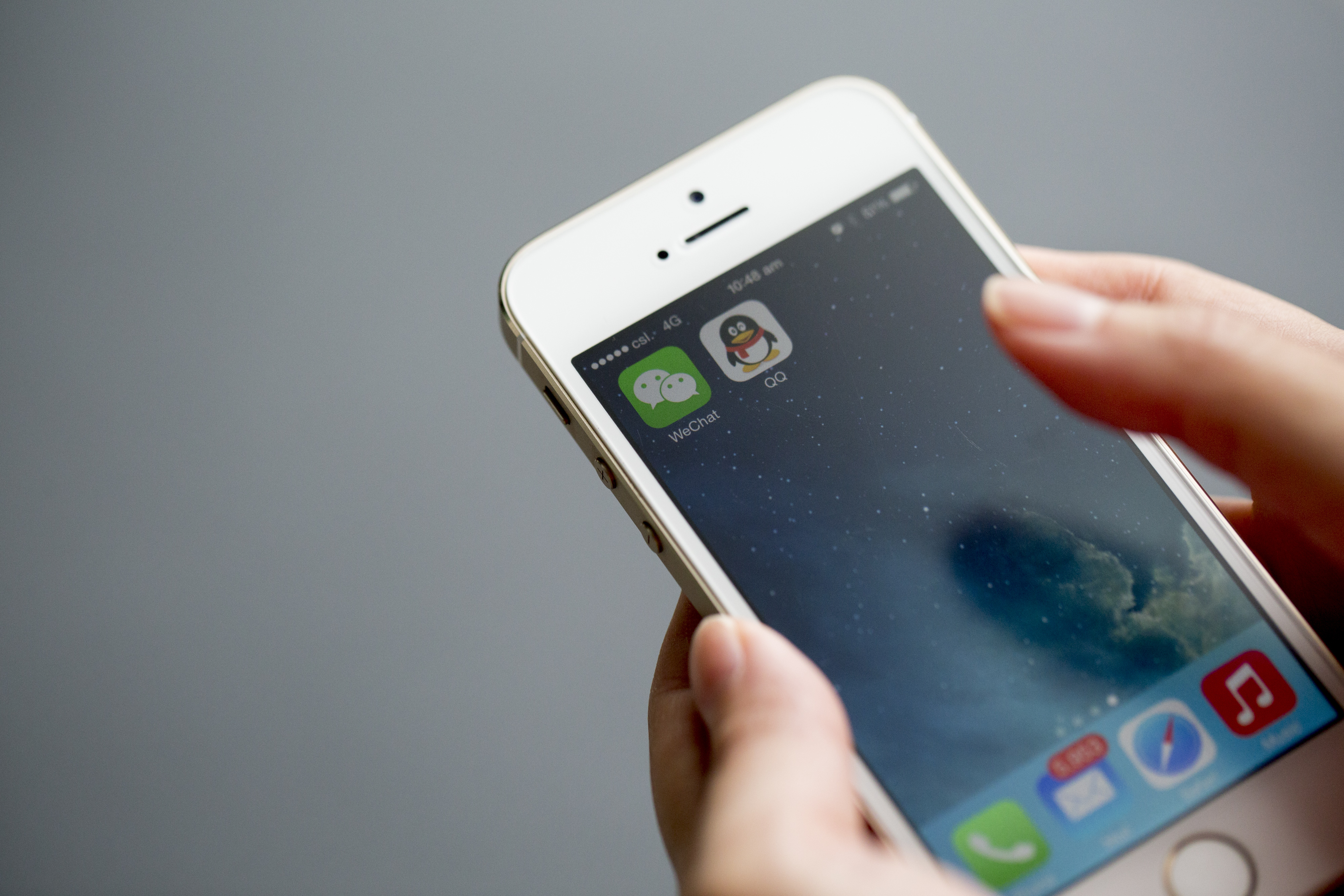 The icons for Tencent Holdings Ltd.'s messaging applications WeChat, left, and QQ are displayed on an Apple Inc. iPhone 5s.