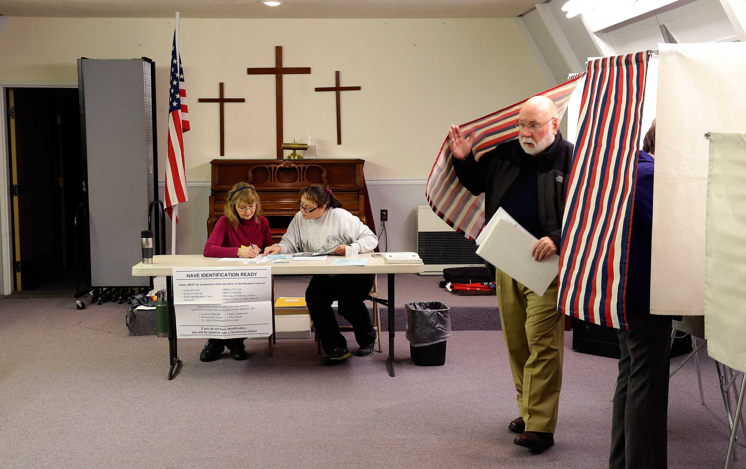 A voter leaves his booth as election workers GayLee Erickson, left, and Debbie Redmond, second from left, confer at the Valley Bible Chalet, in Indian, Alaska on Nov. 4, 2014.