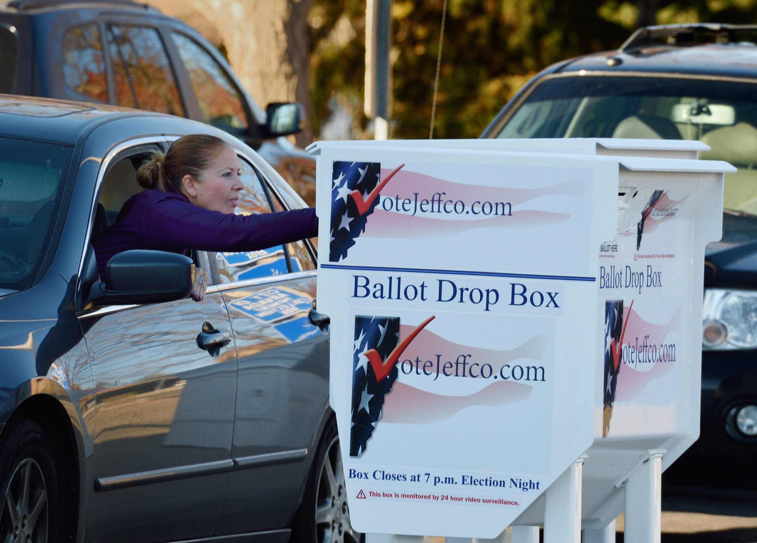A voter drops her election ballot at one of many ballot drop boxes in the Arvada suburb of Denver on Nov. 4, 2014.