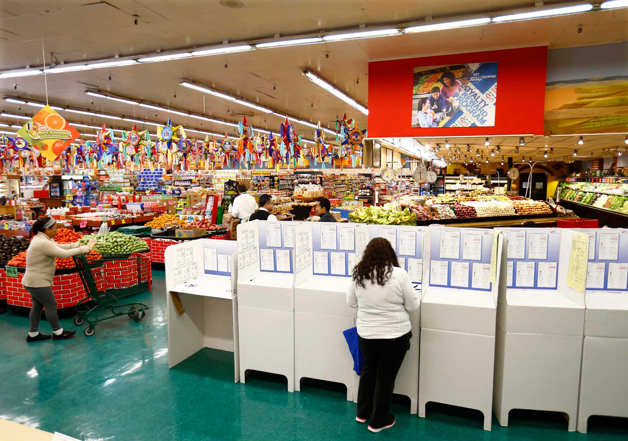 A woman votes at a polling station inside a local grocery store in National City, Calif. on Nov. 4, 2014.