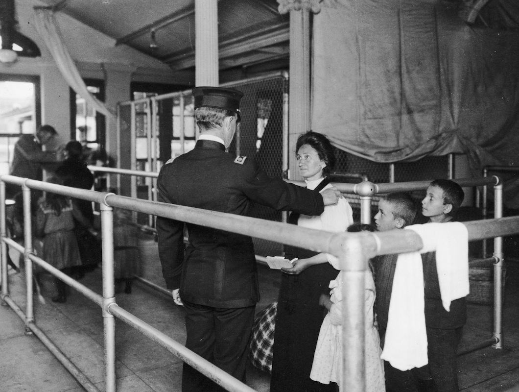 An immigration officer talking to an immigrant with her children on Ellis Island, New York, circa 1880