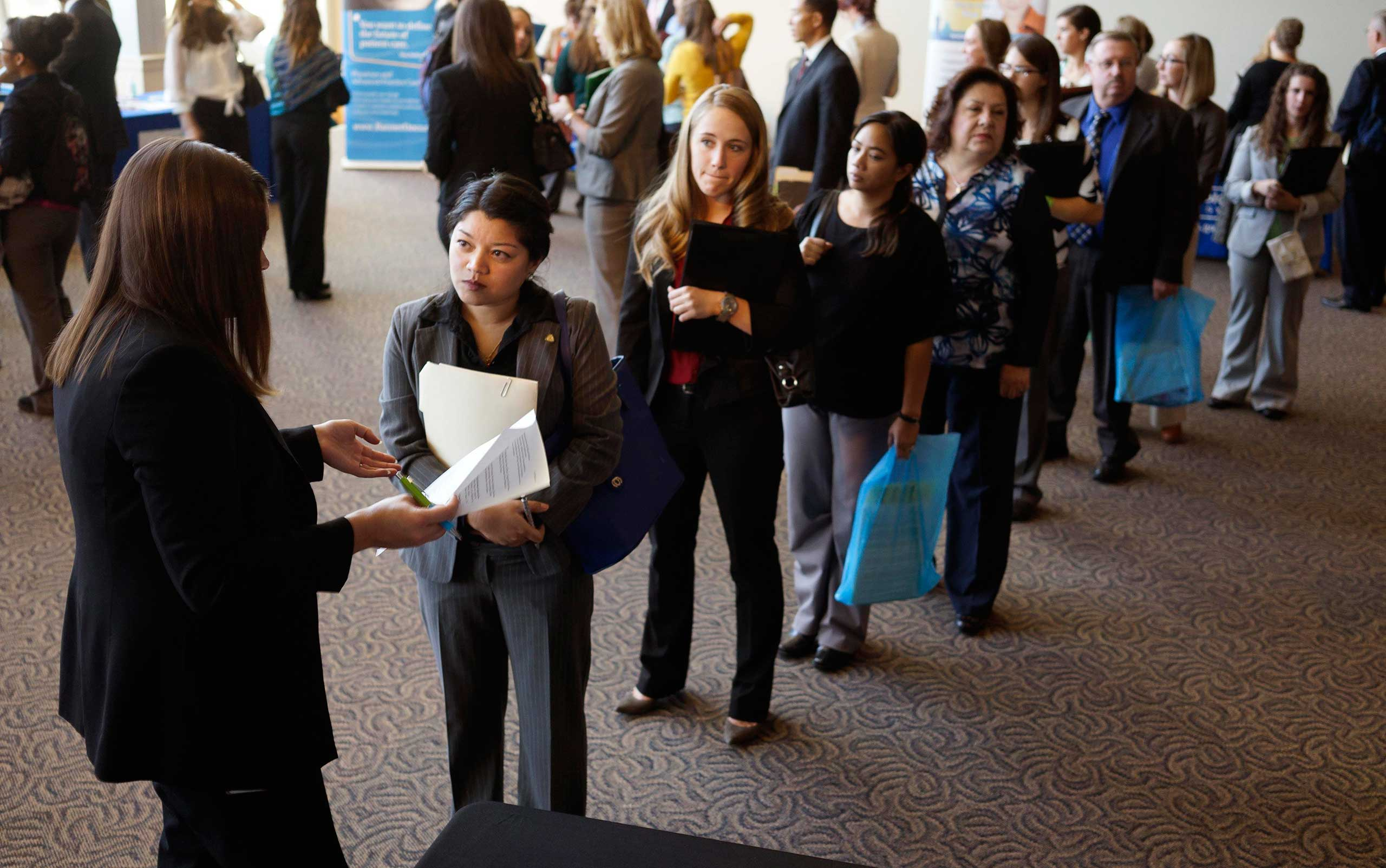 Jobseekers wait to talk to a recruiter at the Colorado Hospital Association's health care career event in Denver, Oct. 13, 2014.