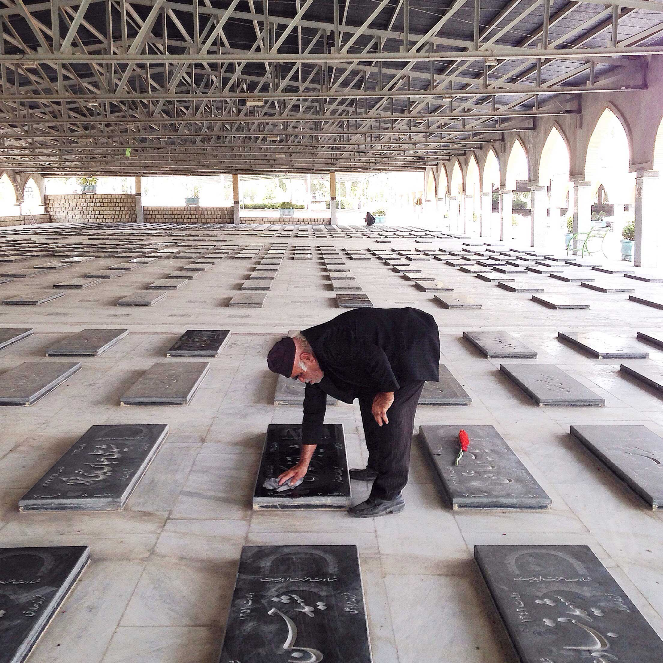 An elderly man dusts off the tombstone of his son, killed in the Iran-Iraq War. Tehran, Iran.