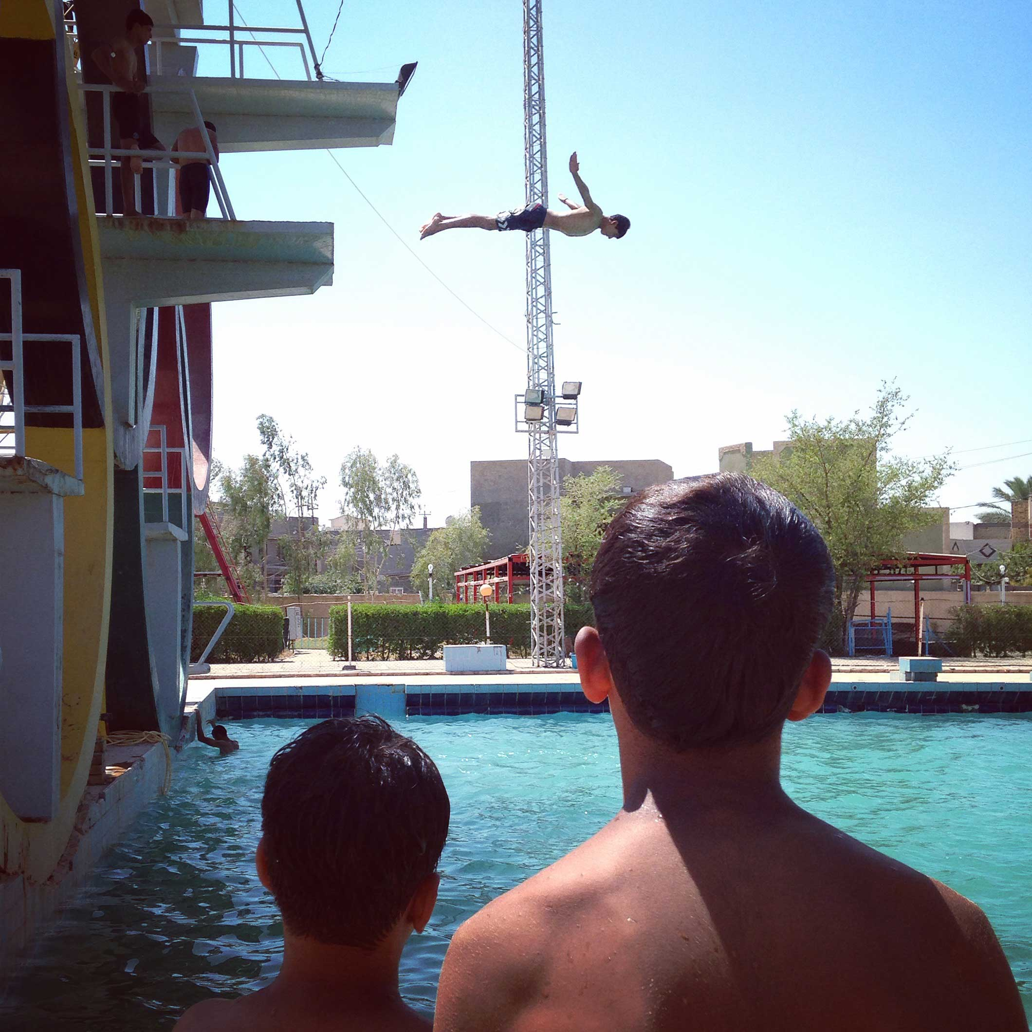 Iraqi young man jumps into a public swimming pool during a hot day in the city of Hilla, Babil, Iraq.