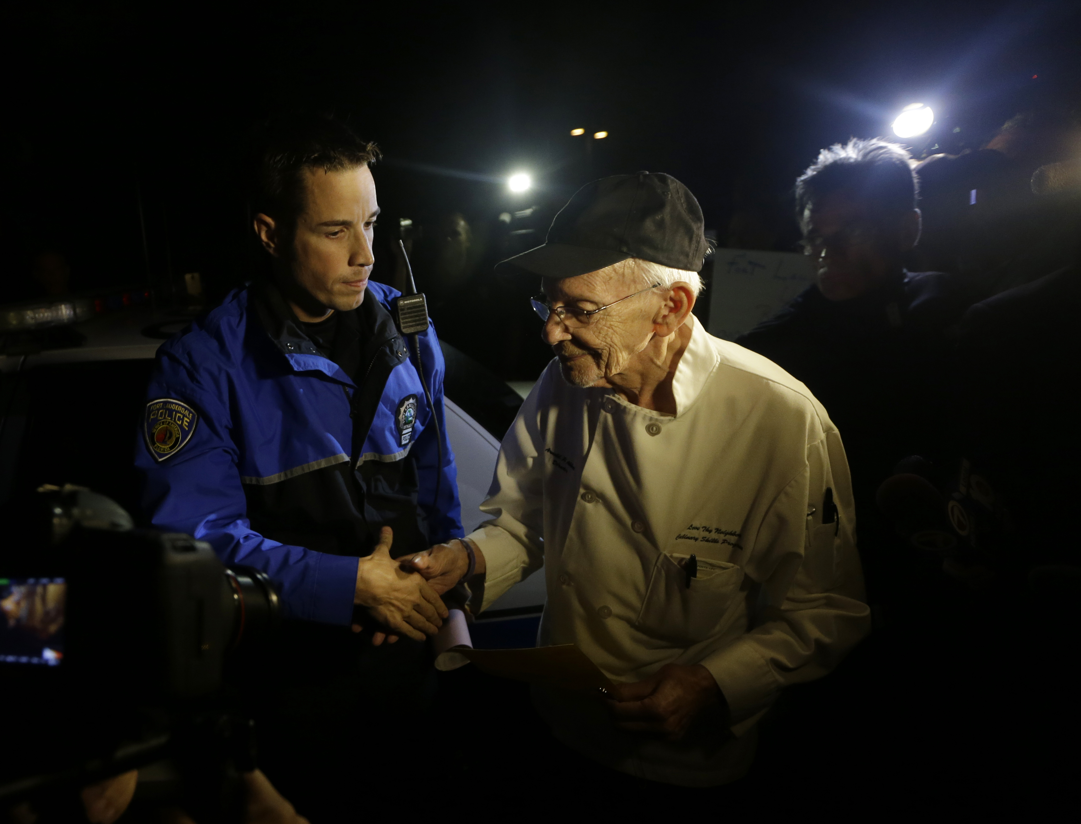 Homeless advocate Arnold Abbott, 90, of the nonprofit group Love Thy Neighbor Inc.,right, shakes hands with a Fort Lauderdale police officer, left, Wednesday, Nov. 5, 2014, in Fort Lauderdale, Fla. Abbott and a group of volunteers were feeding the homeless in a public parking lot next to the beach when he was issued a summons to appear in court for violating an ordinance that limits where charitable groups can feed the homeless on public property.