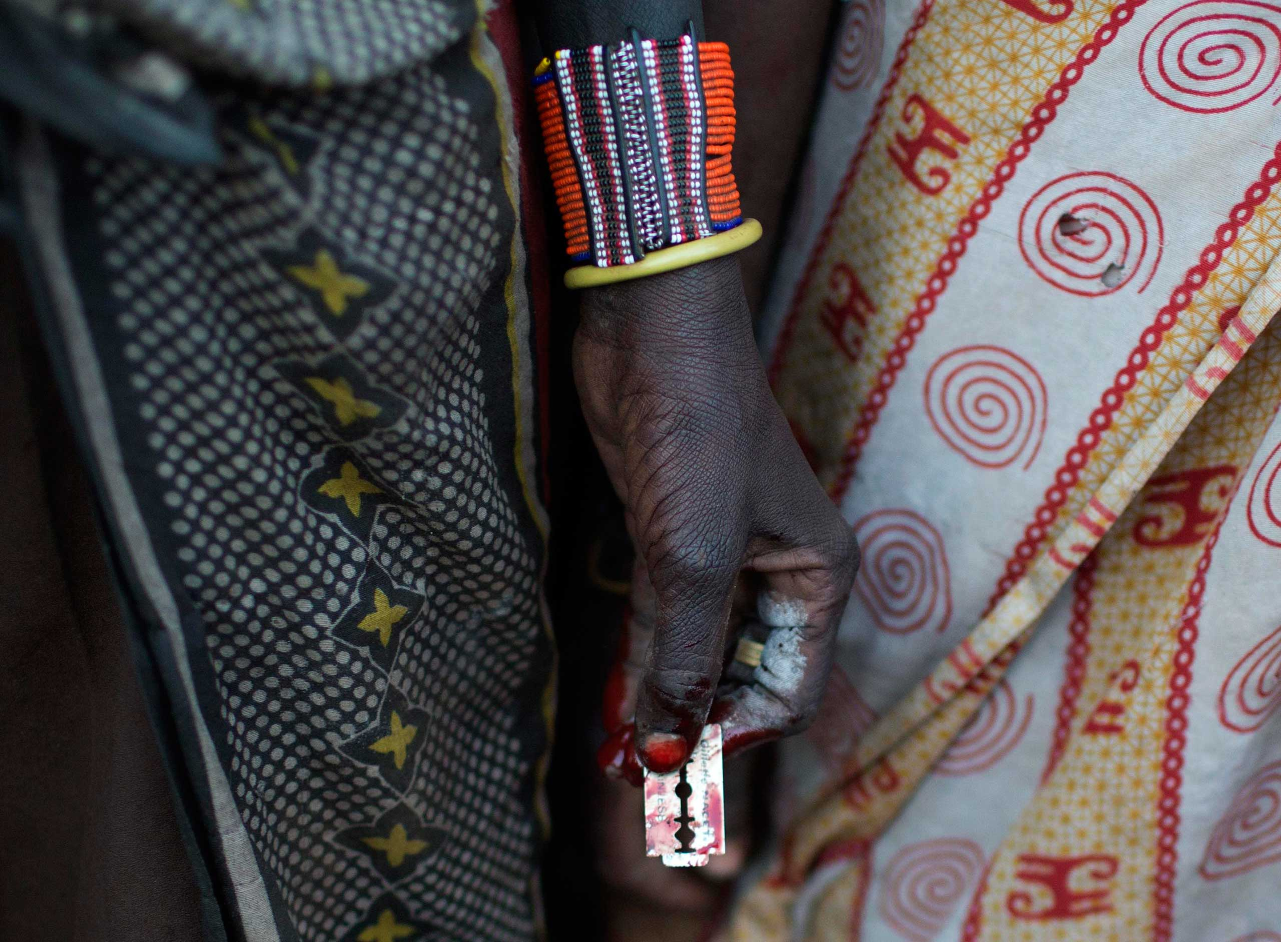 A Pokot woman holds a razor blade after performing a circumcision on four girls in a village about 80 kilometres from the town of Marigat in Baringo County, Kenya, Oct. 16, 2014.