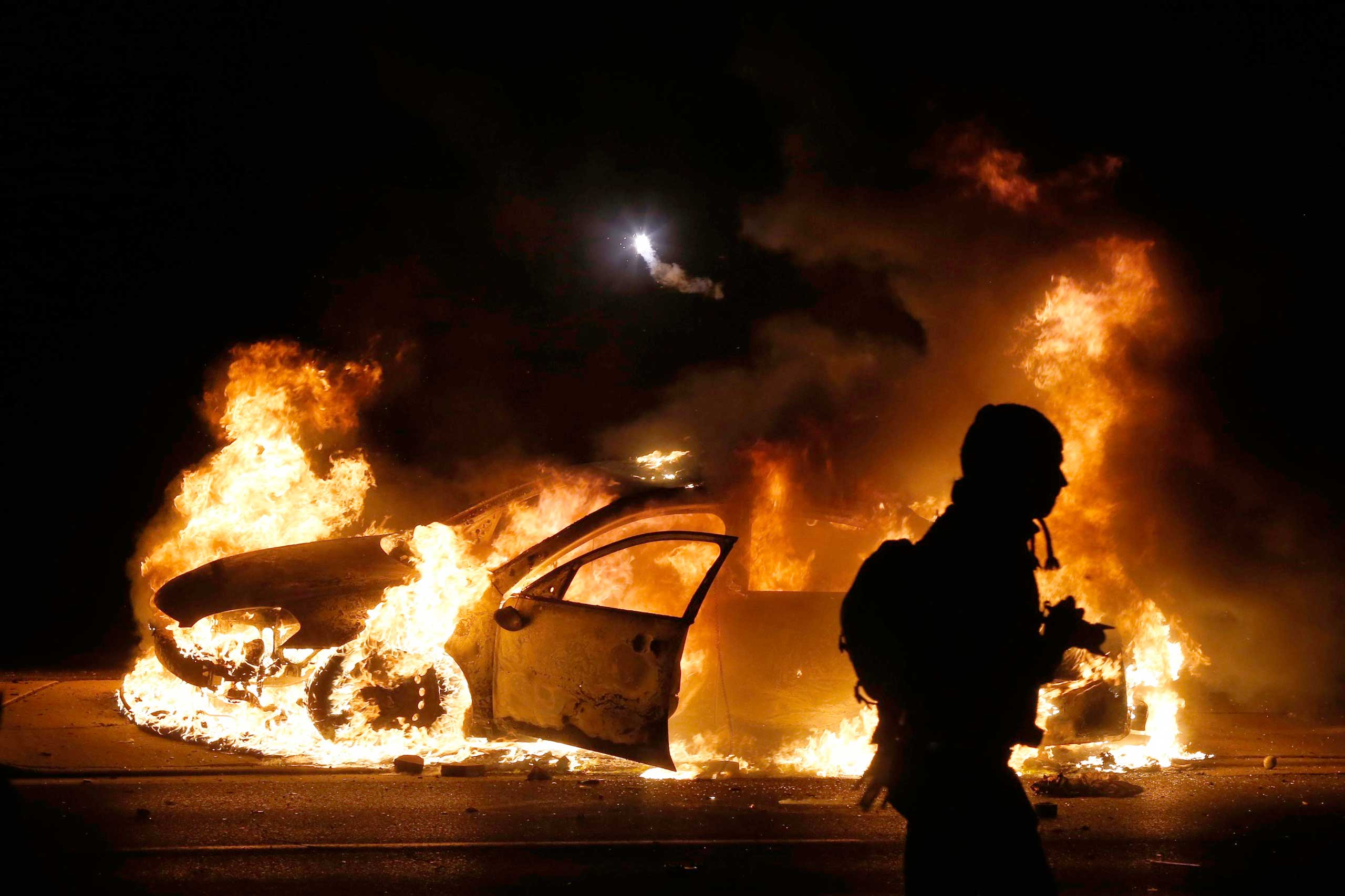 After the announcement that the grand jury brought no charges against Darren Wilson, police officers and protesters faced off on a tense night in which cars and buildings were burned by protesters and tear gas thrown by police, in Ferguson, Mo. on Nov. 24, 2014.