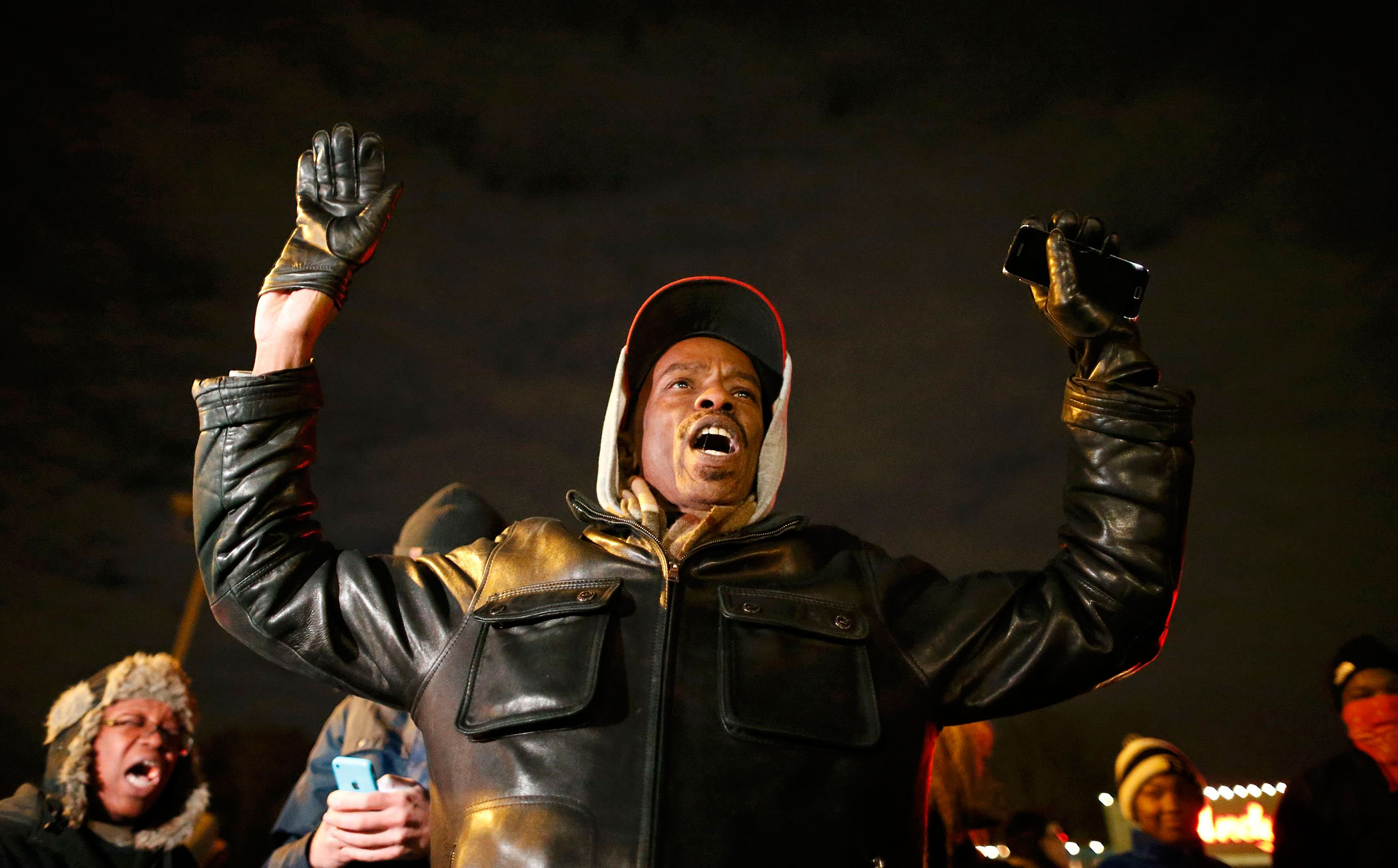 A protester holds his hands in the air outside the Ferguson Police Department in Ferguson, Missouri, November 24, 2014.