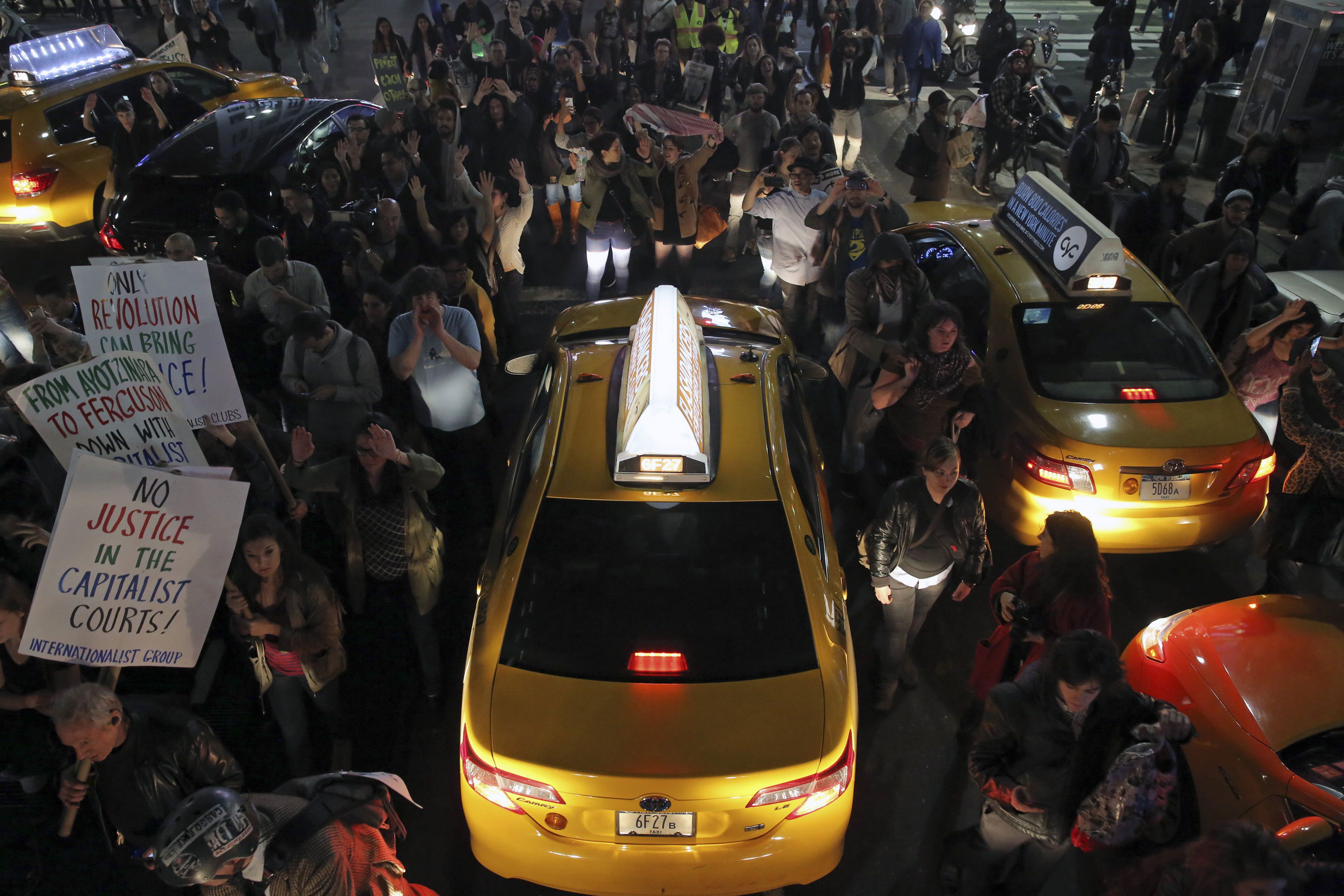 Protesters march around taxis near Times Square in New York City on Nov. 24, 2014.