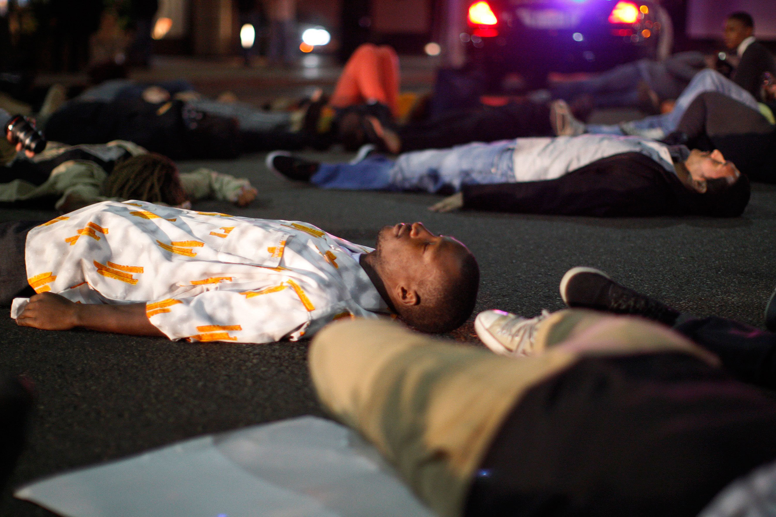 Protesters lay down to block traffic in the intersection of Wilshire Boulevard and Rodeo Dr. in Beverly Hills, Calif., on Nov. 24, 2014.
