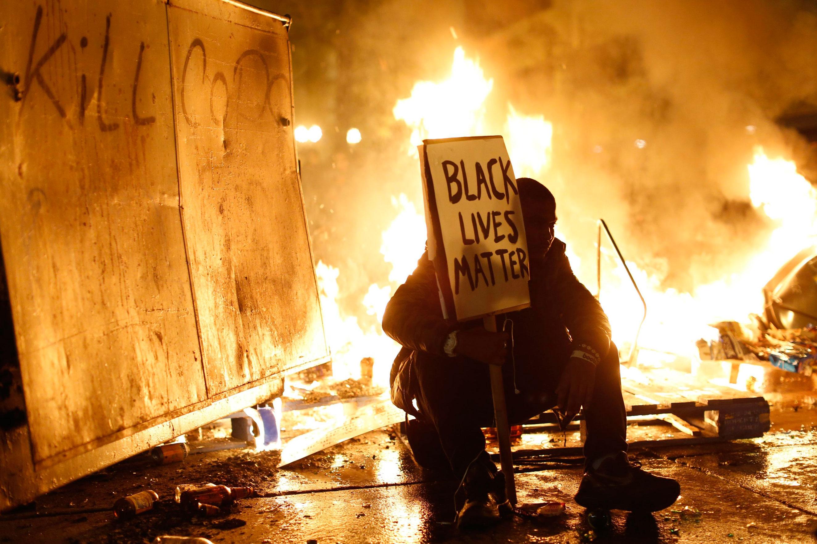 Flames burn behind a demonstrator in Oakland, Calif., on Nov. 25, 2014.