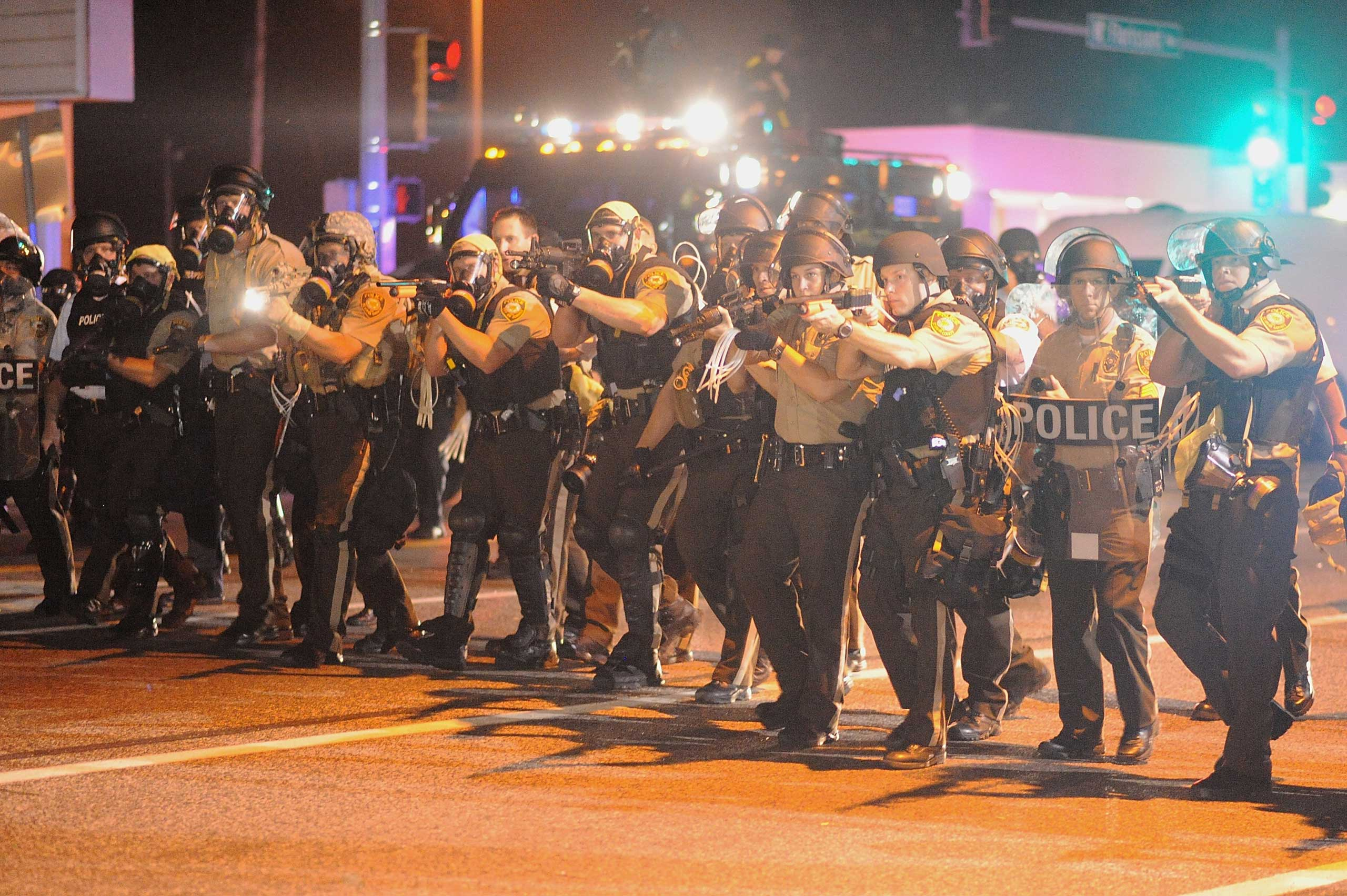 Law enforcement officers look on during a protest on West Florissant Avenue in Ferguson on Aug. 18, 2014.