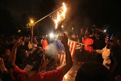 Several American flags are burned during a night of protest after a candlelight vigil for Vonderrit Myers, Jr. in St. Louis on Oct. 8, 2014.