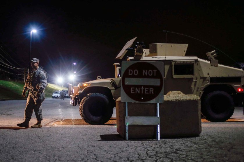 Member of the National Guard stands along a parked military vehicle in the back of a shopping center in Ferguson, Missouri